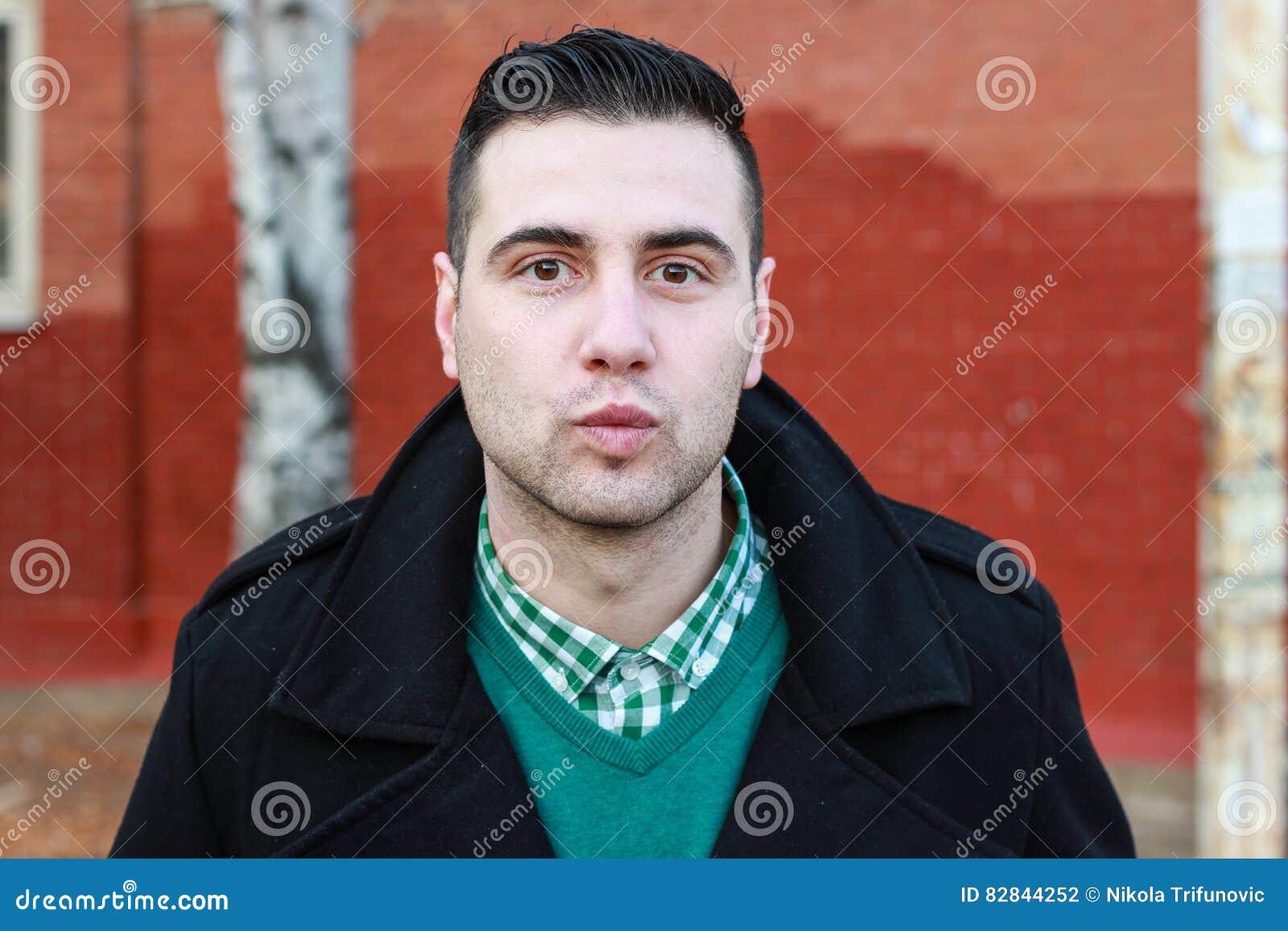 Homem considerável novo no revestimento preto do inverno que envia um beijo