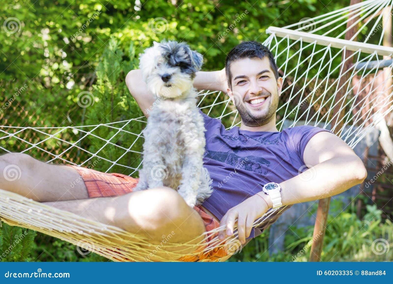 Homem considerável novo que relaxa na rede com seu cão branco