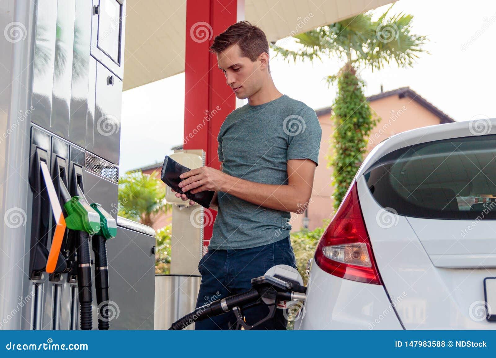 Homem considerável novo que verifica sua carteira durante o reenchimento da gasolina
