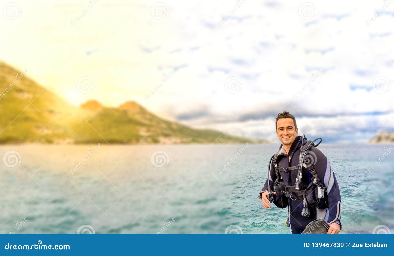Homem considerável novo sorriso isolado do mergulhador pronto para ir mergulho autônomo no terno molhado de água fria, nas aletas