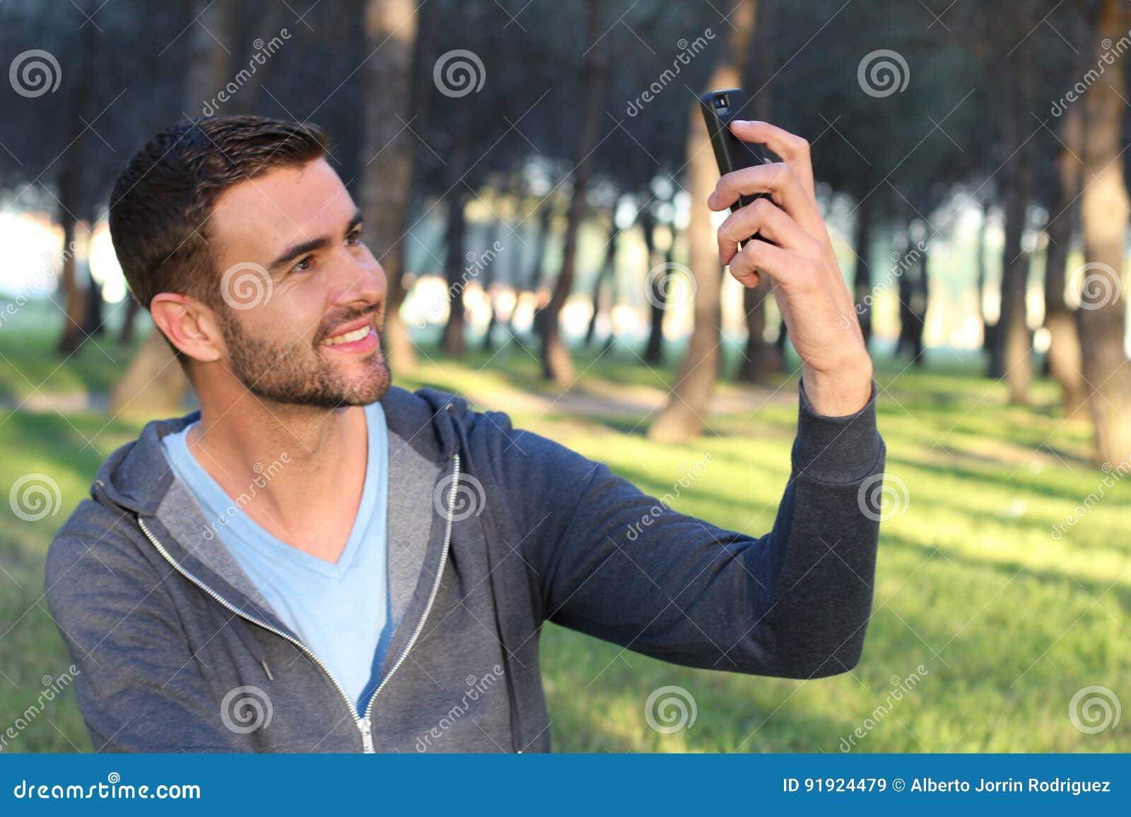 Homem considerável que agarra um PIC com seu telefone celular