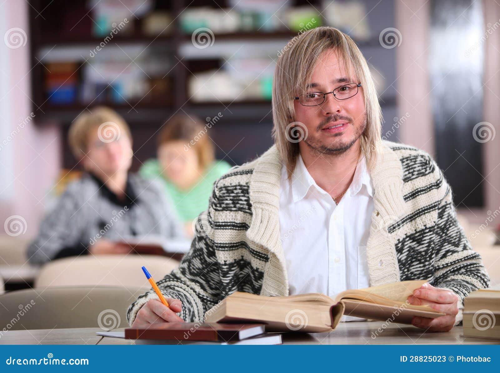 Homem considerável que estuda na mesa com lotes dos livros