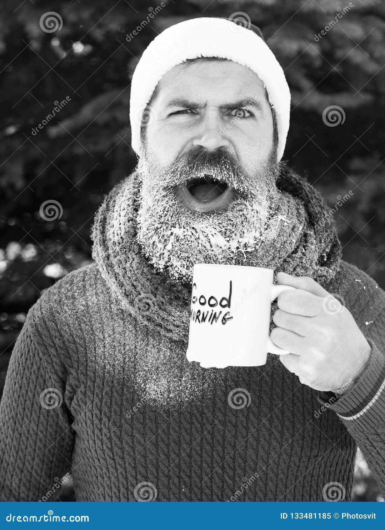 Homem considerável surpreendido no chapéu de Papai Noel, no moderno farpado com barba e nas bebidas do bigode do copo com bom dia