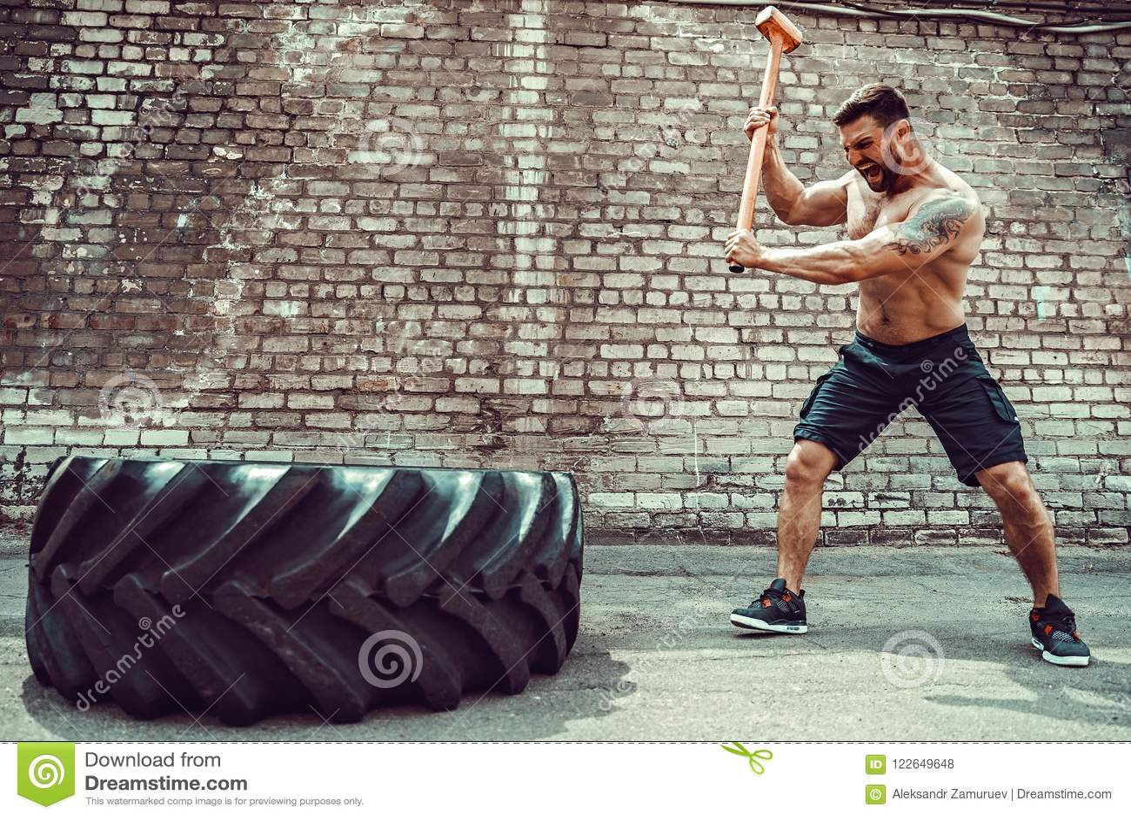 Homem da aptidão do esporte que bate o pneu da roda com treinamento de Crossfit do pequeno trenó do martelo