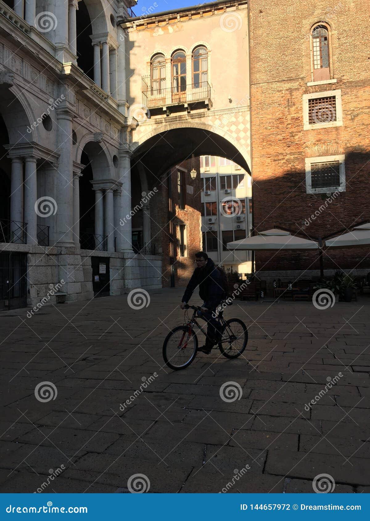 Homem da bicicleta sob uma ponte em Roma