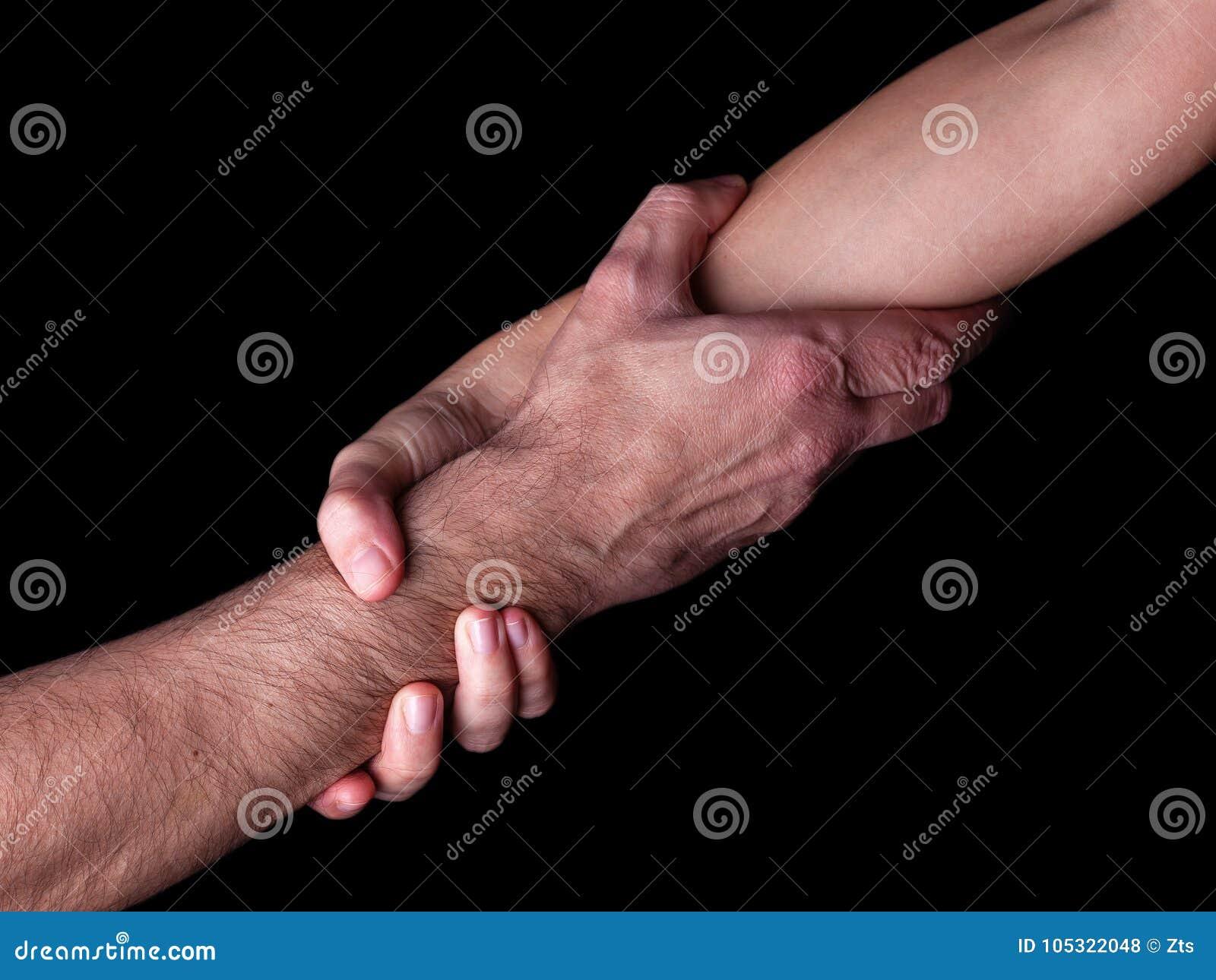Homem da economia da mulher, do salvamento e da ajuda guardando ou griping o antebraço Mão fêmea e braço que levantam o homem