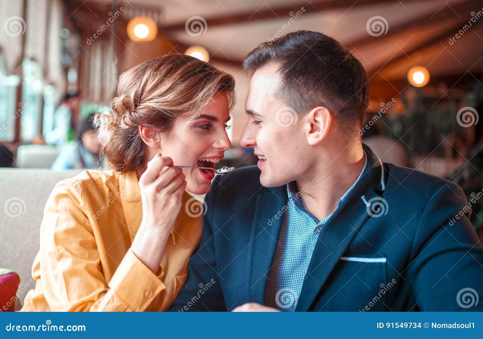 Homem de alimentação da jovem mulher com uma colher