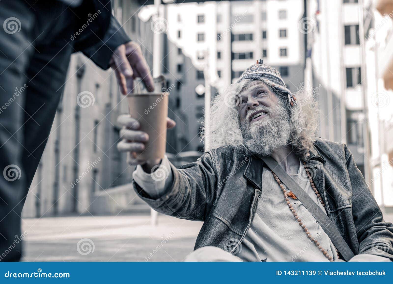 Homem de cabelos compridos afligido que é desabrigado pobre e que recolhe o dinheiro