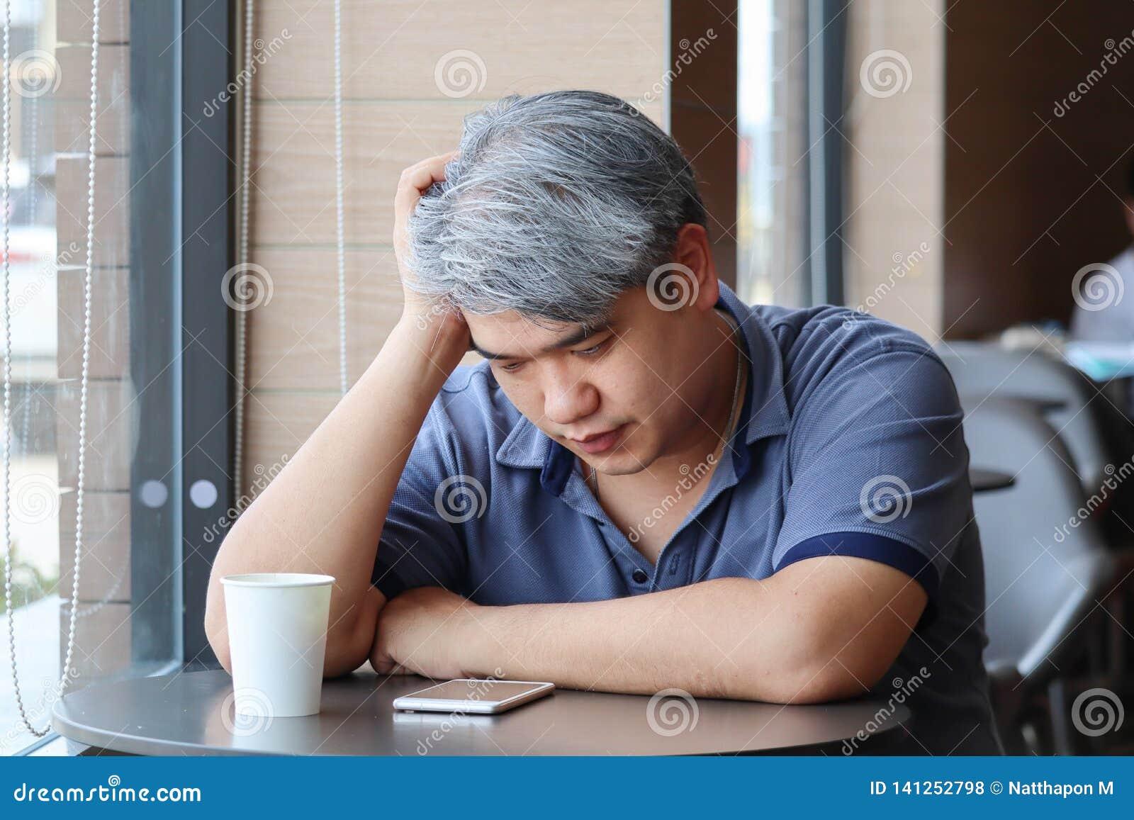 Homem de meia idade asiático novo cansado Stressed, mão da tomada do ancião na depressão do sentimento da cabeça e assento esgota