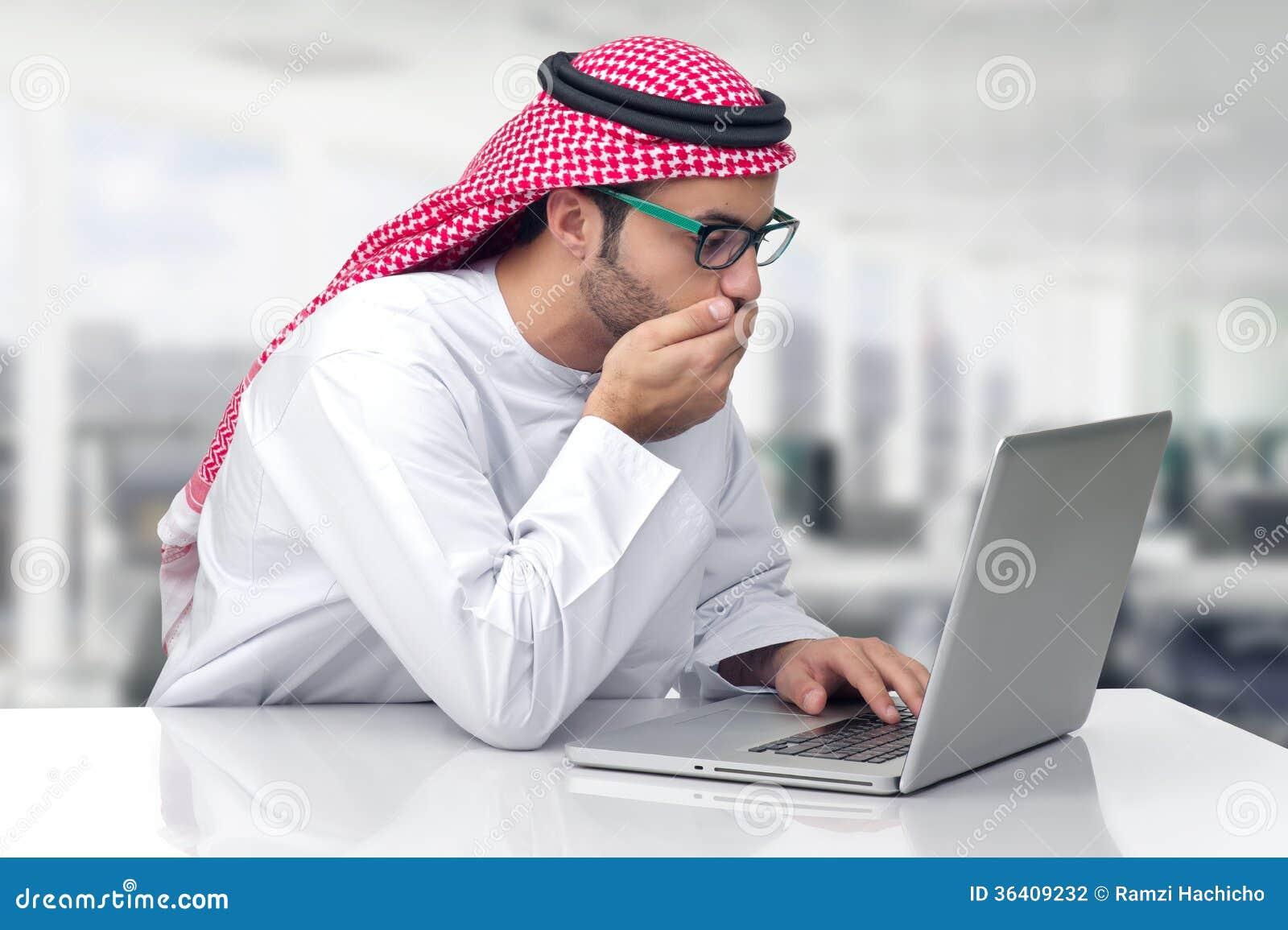 Homem de negócio árabe que olha chocado em seu computador