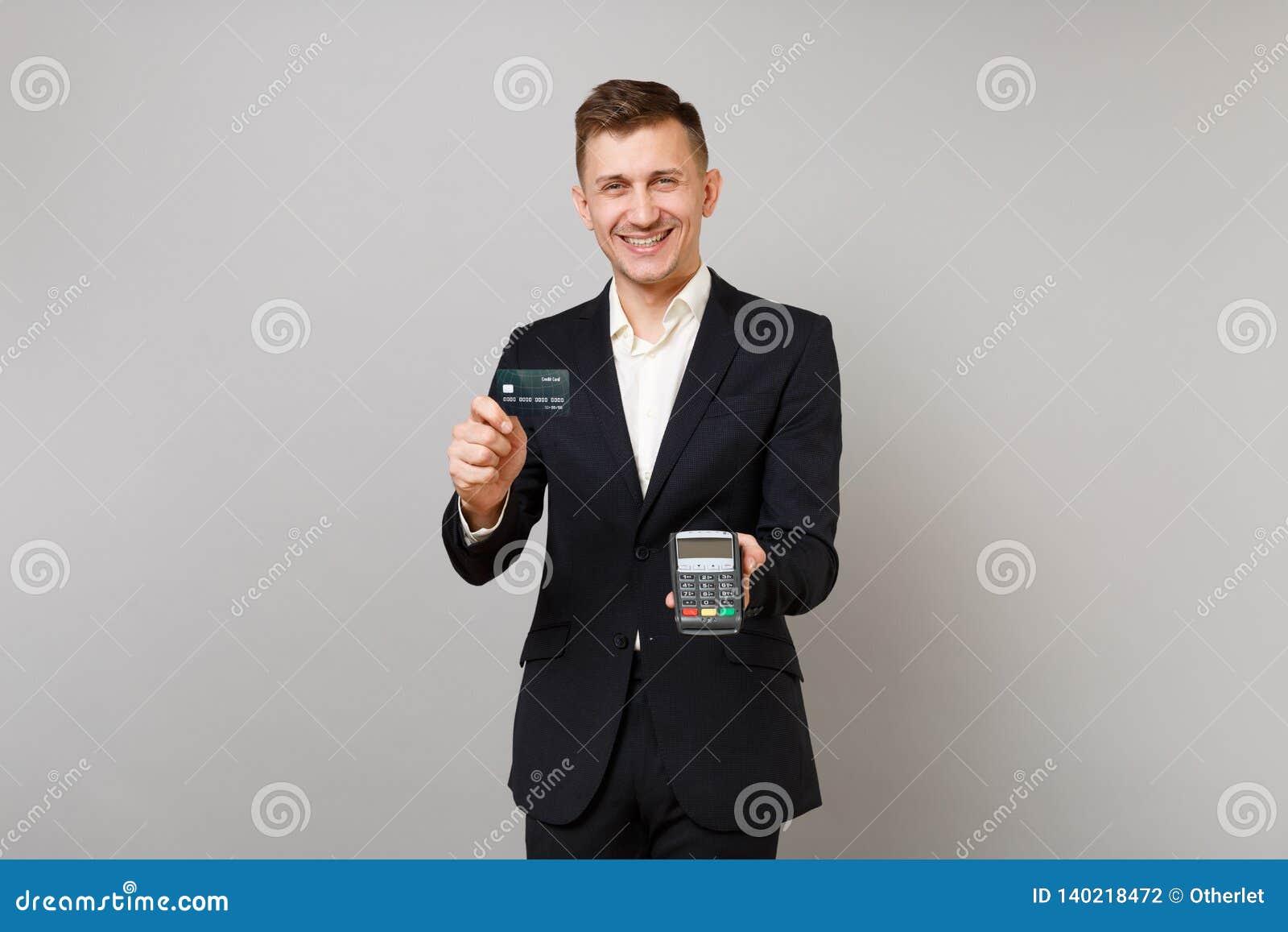 Homem de negócio alegre que guarda o terminal moderno sem fio do pagamento do banco para processar e adquirir os pagamentos com c