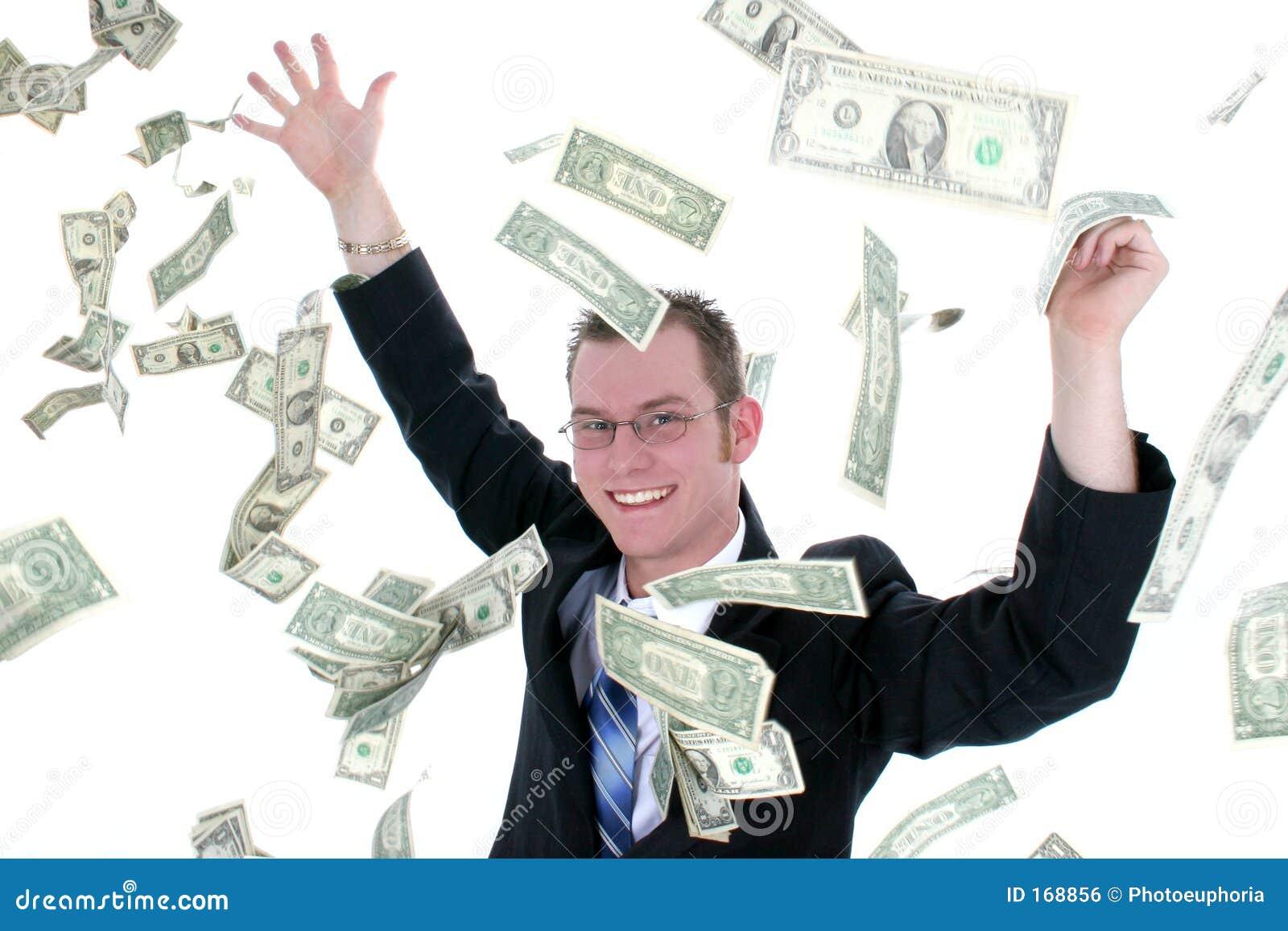 Homem de negócio atrativo no dinheiro de jogo do terno no ar