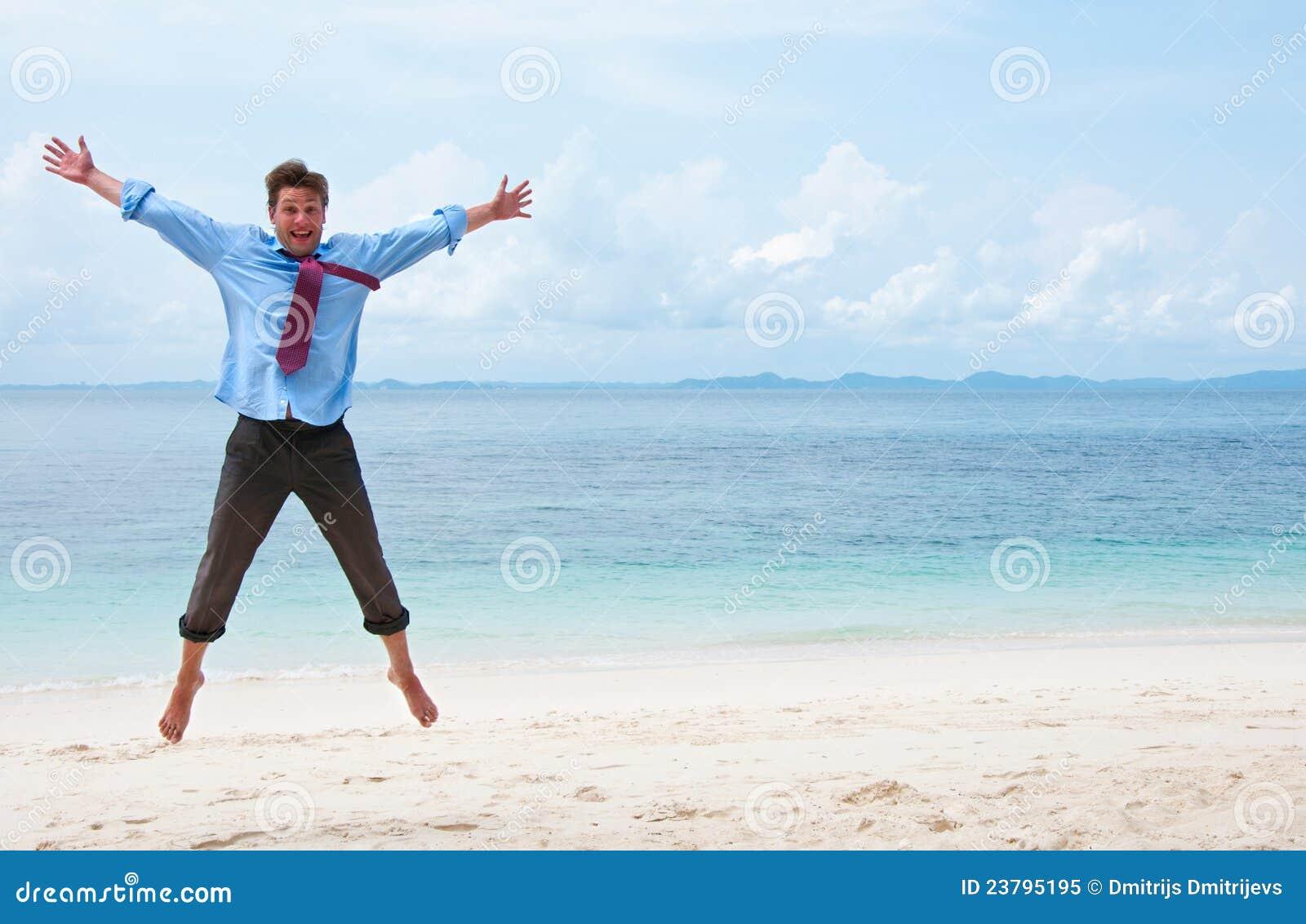 Homem de negócio engraçado que salta na praia