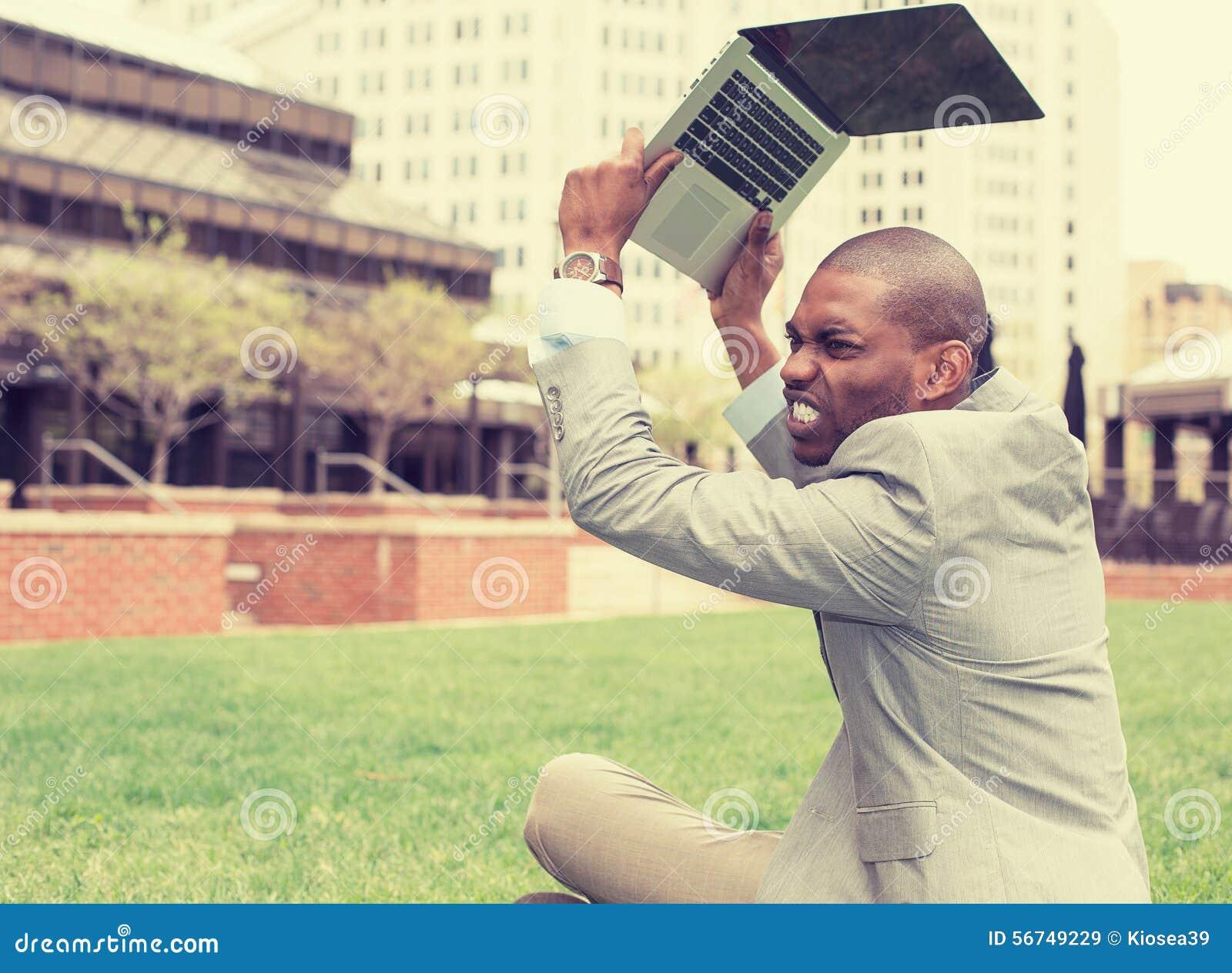 Homem de negócio irritado que joga seu tablet pc, portátil
