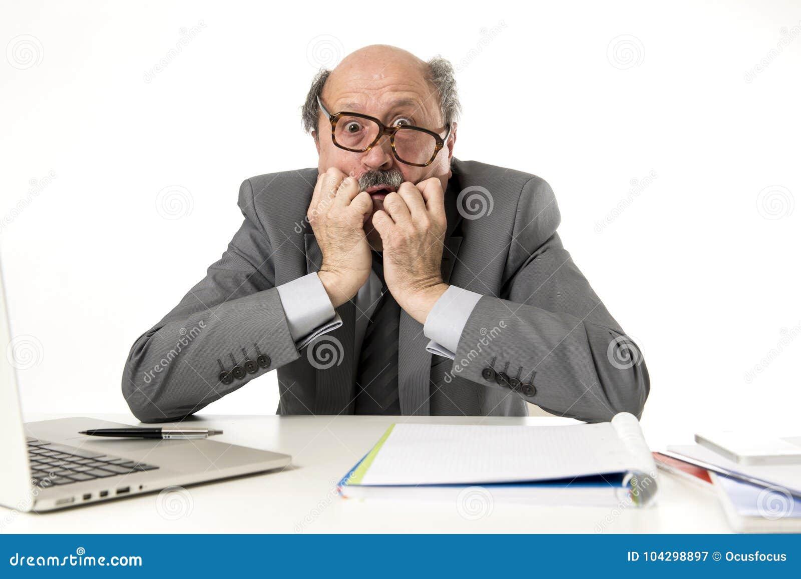 Homem de negócio maduro com cabeça calva em seu funcionamento 60s forçado e frustrado em parecer desesperado da mesa do portátil