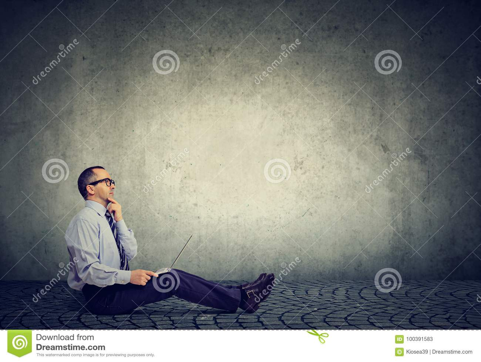 Homem de negócio maduro com o portátil que senta-se em um pensamento do assoalho