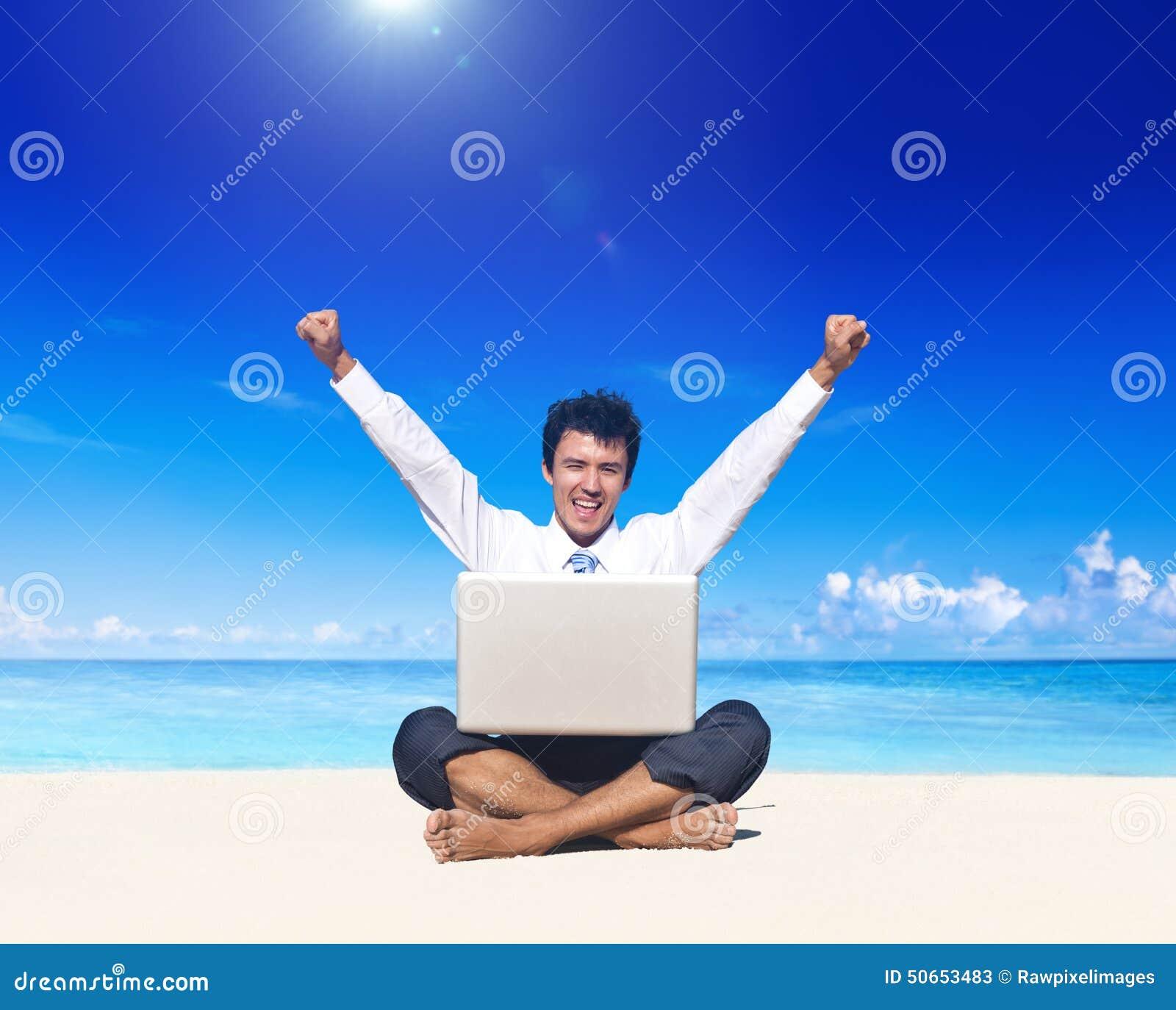 Homem de negócio na praia com portátil