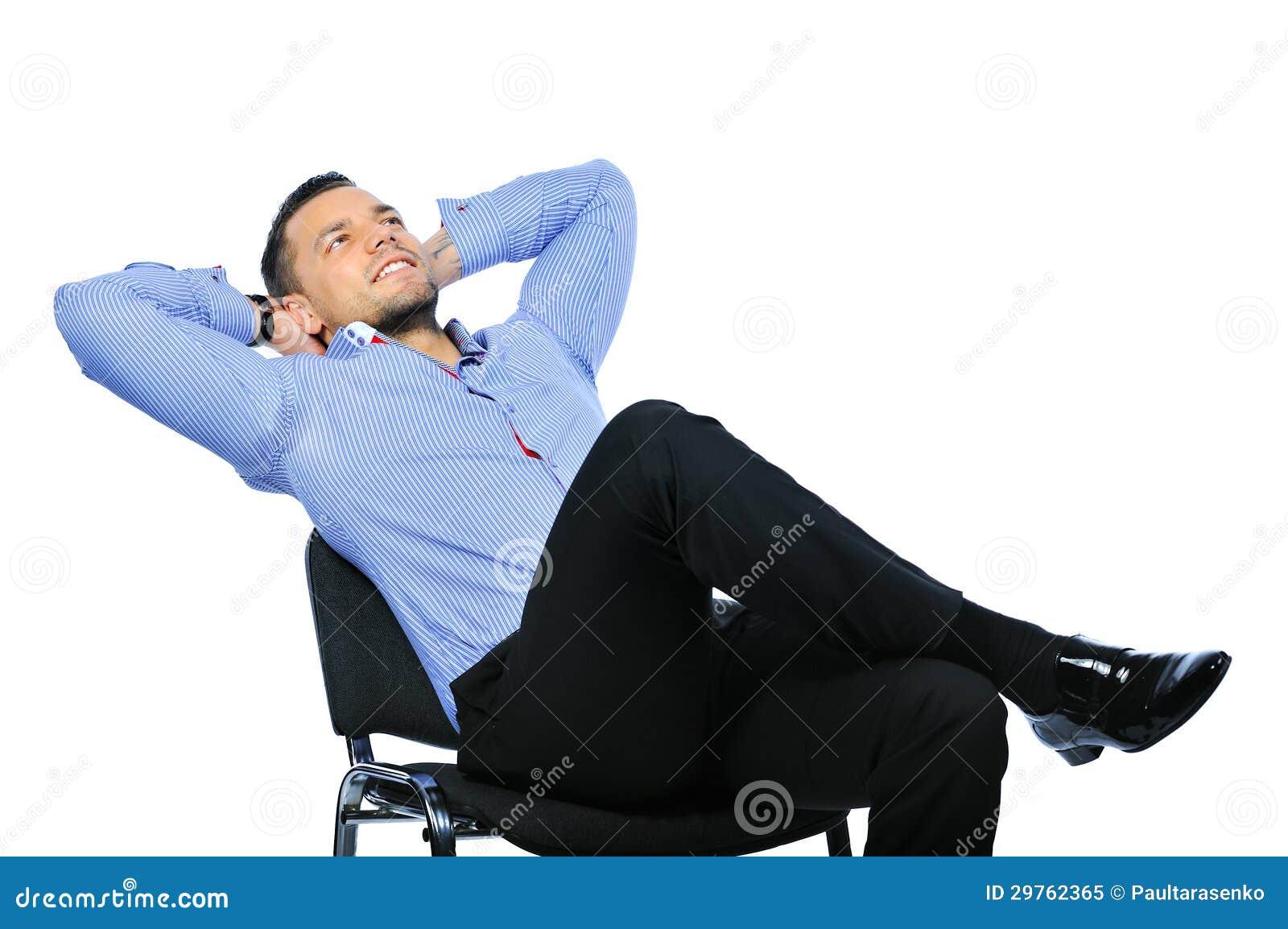 Homem de negócio novo que relaxa na cadeira