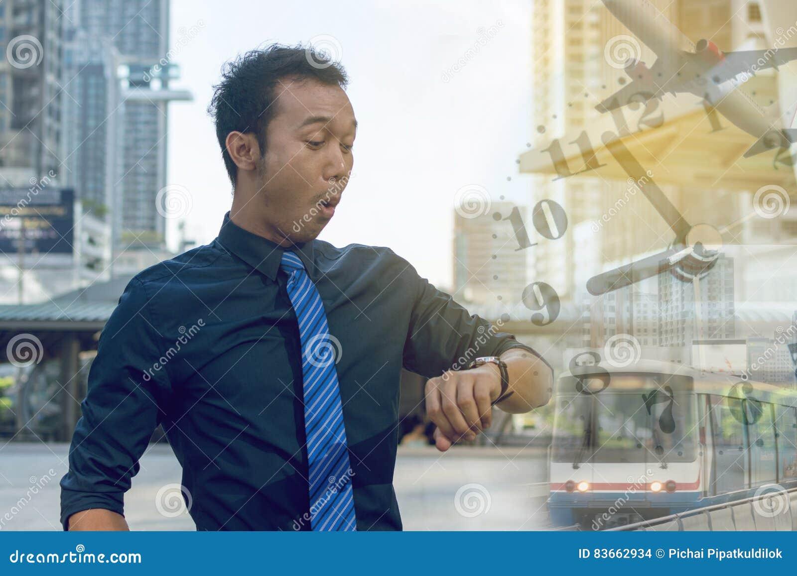 Homem de negócio novo que verifica o tempo em seu relógio o tempo aplana t