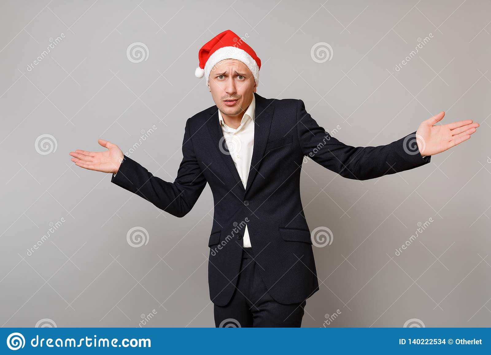 Homem de negócio novo referido nas mãos de espalhamento do chapéu preto clássico do Natal do terno isoladas no fundo cinzento