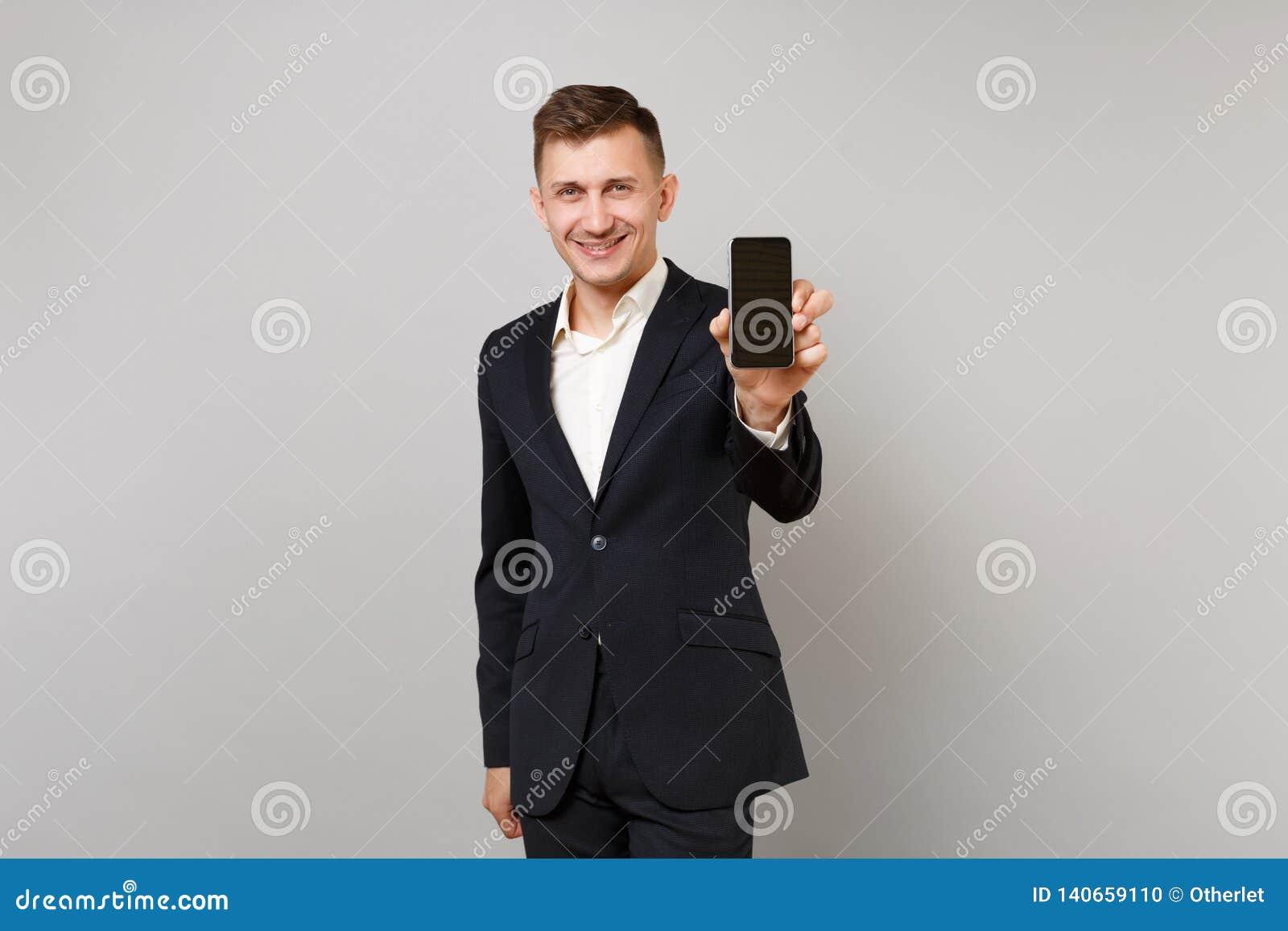 Homem de negócio novo de sorriso no terno preto clássico, telefone celular da terra arrendada da camisa com a tela vazia vazia is