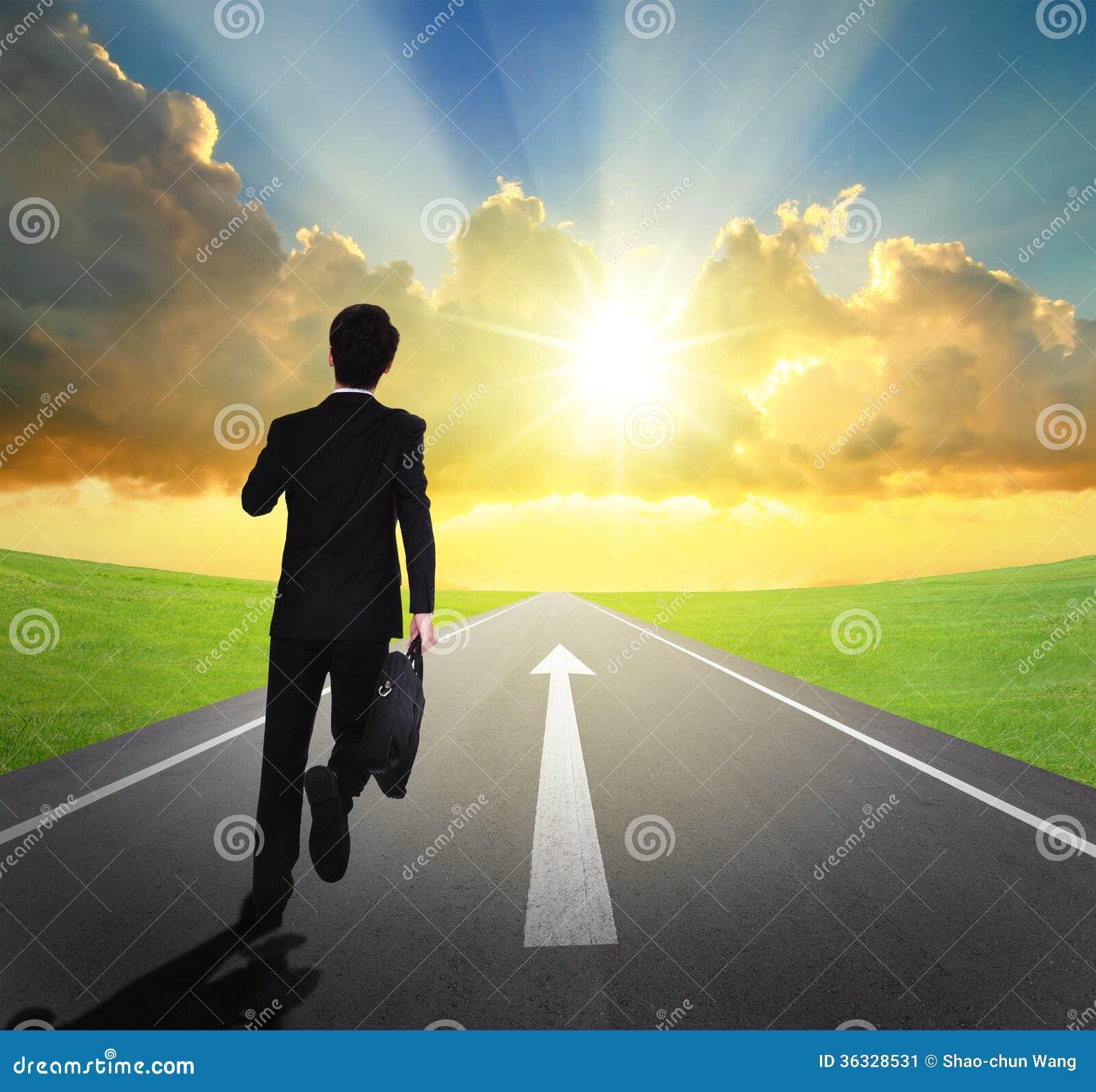 Homem de negócio que corre na estrada asfaltada