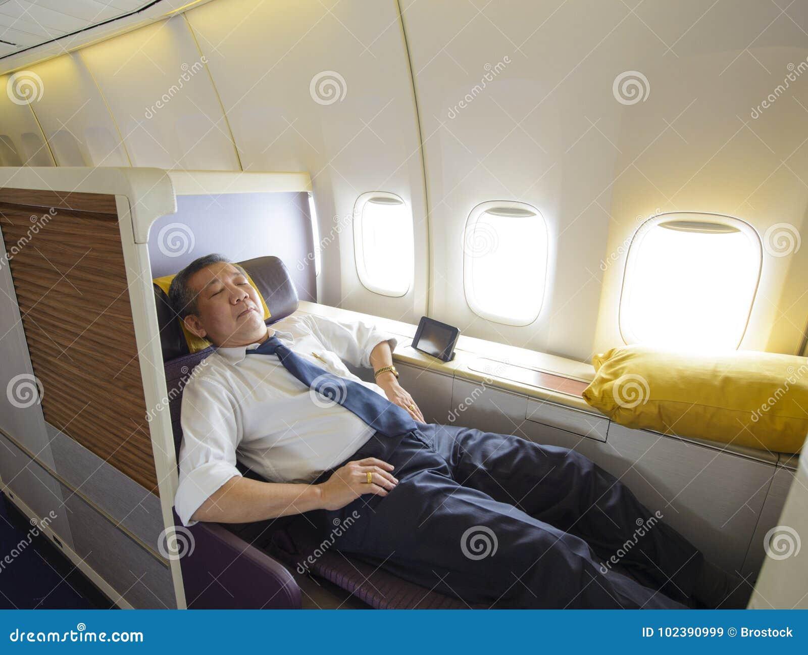 Homem de negócio que dorme na primeira classe de avião no único assento confortável
