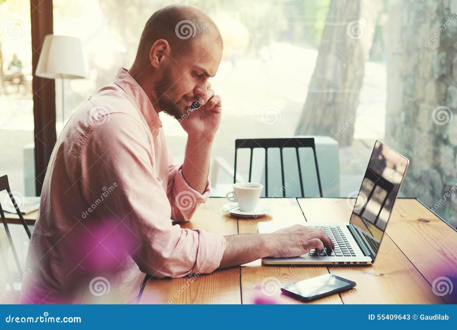 Homem de negócio que fala no telefone esperto e no olhar à tela do portátil