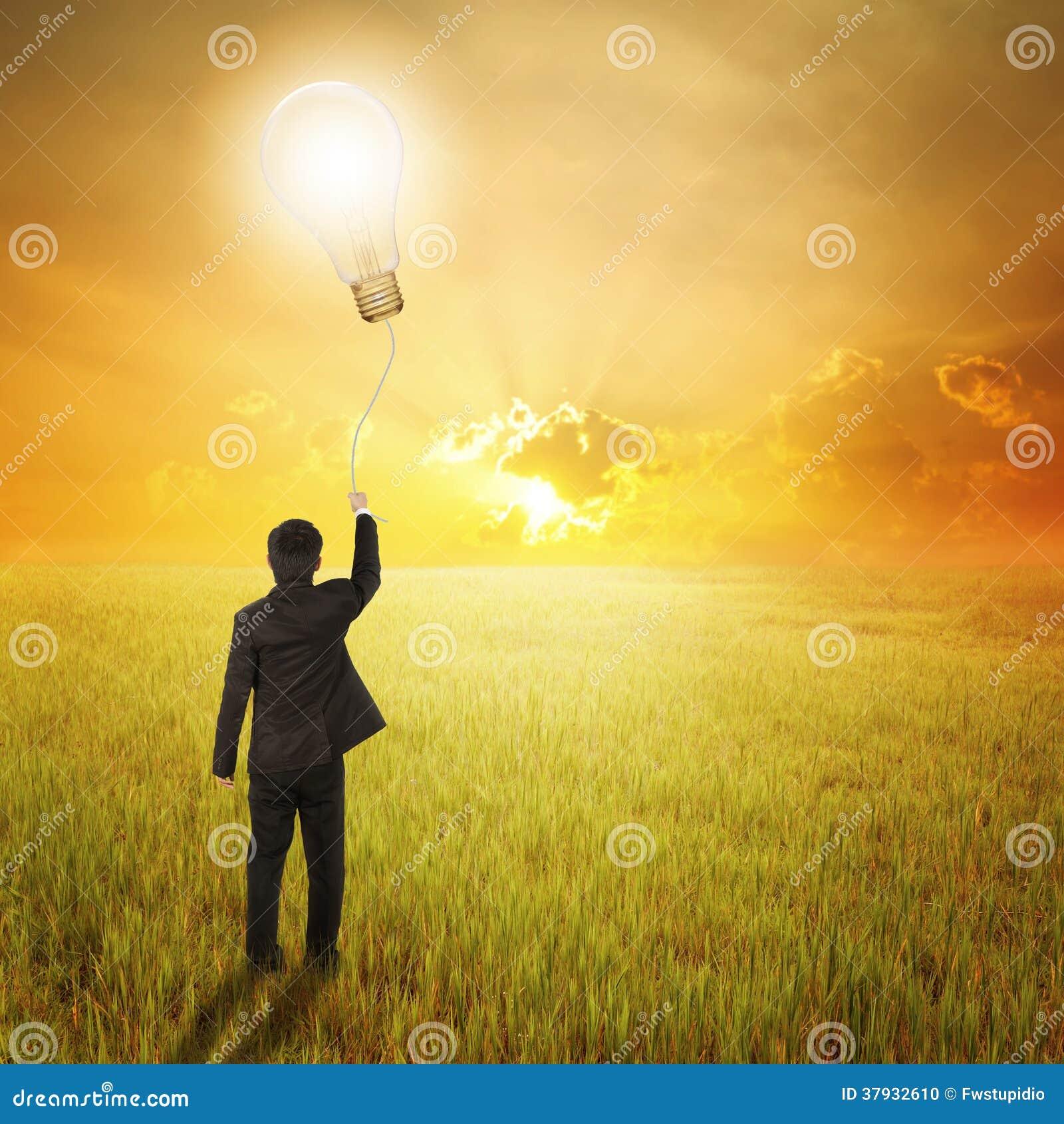 Homem de negócio que guarda o balão do bulbo nos campos e no por do sol