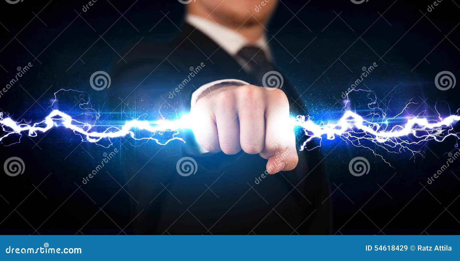 Homem de negócio que guarda o parafuso leve da eletricidade em suas mãos