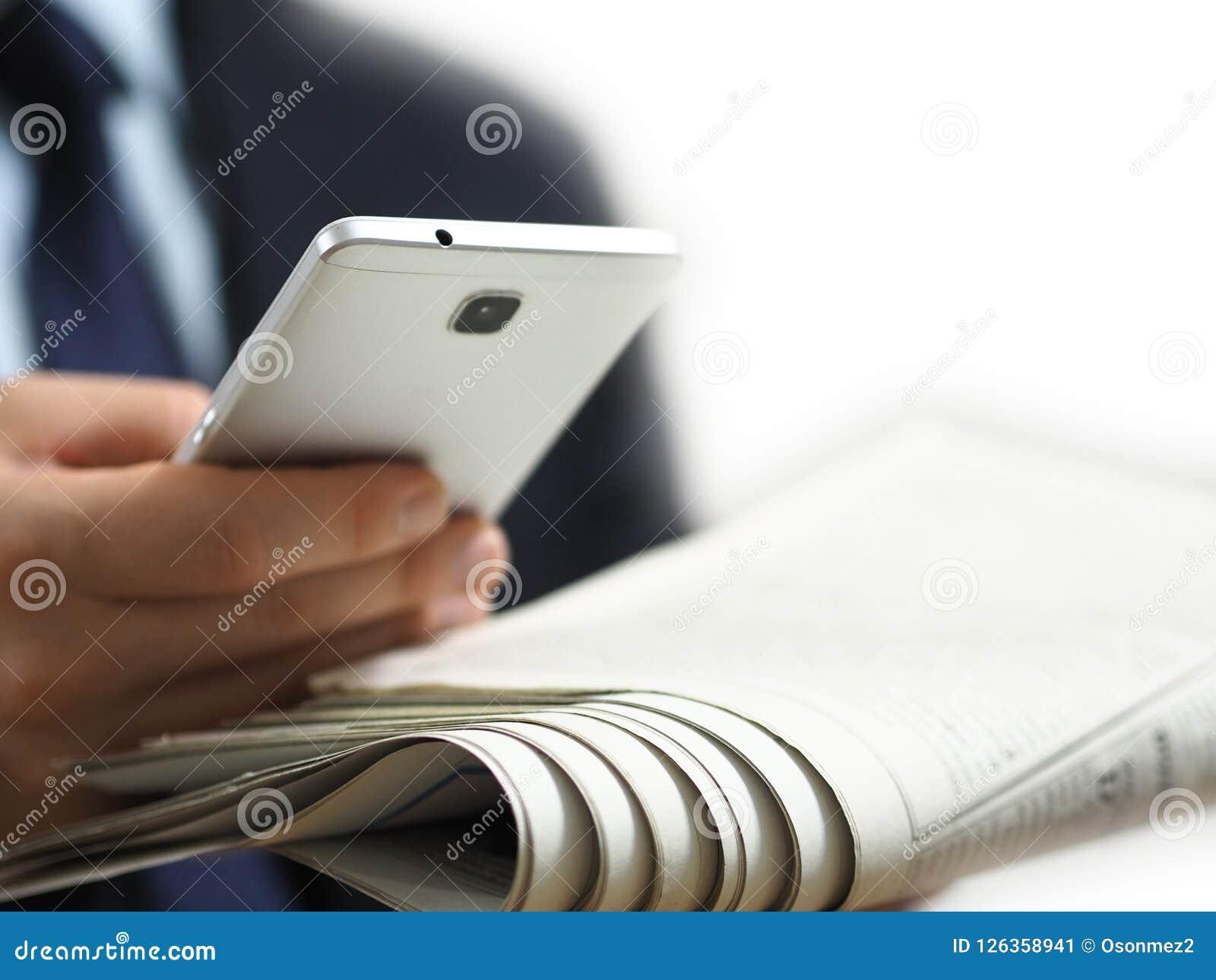 Homem de negócio que guarda um jornal e um telefone esperto em sua mão A imagem de fundo branca