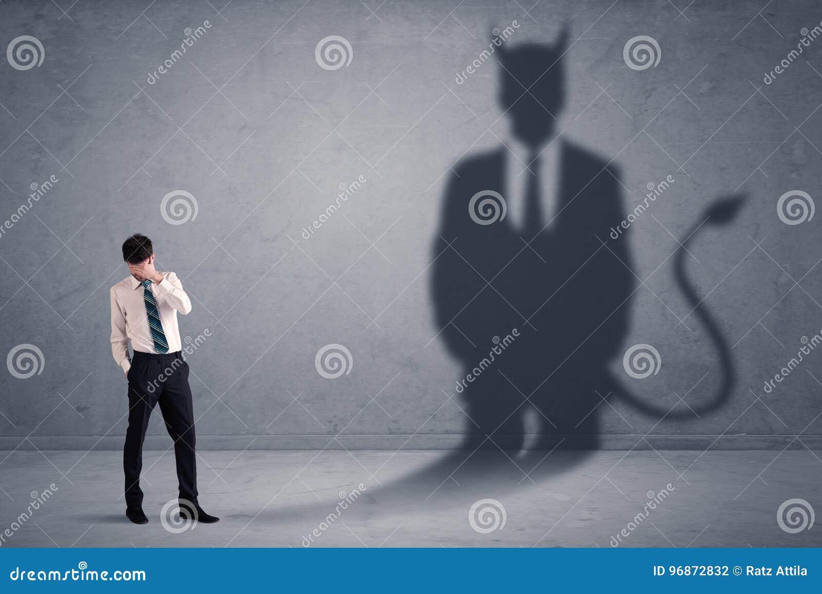 Homem de negócio que olha seu próprio conceito da sombra do demônio do diabo