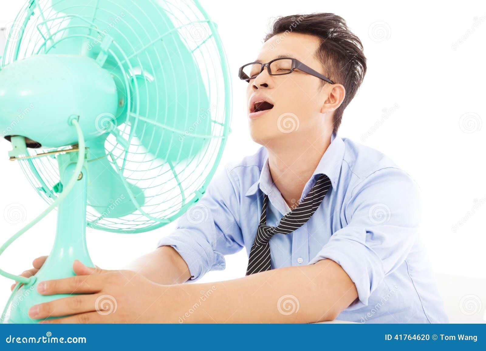 Homem de negócio que sofre um calor quente do verão com fãs