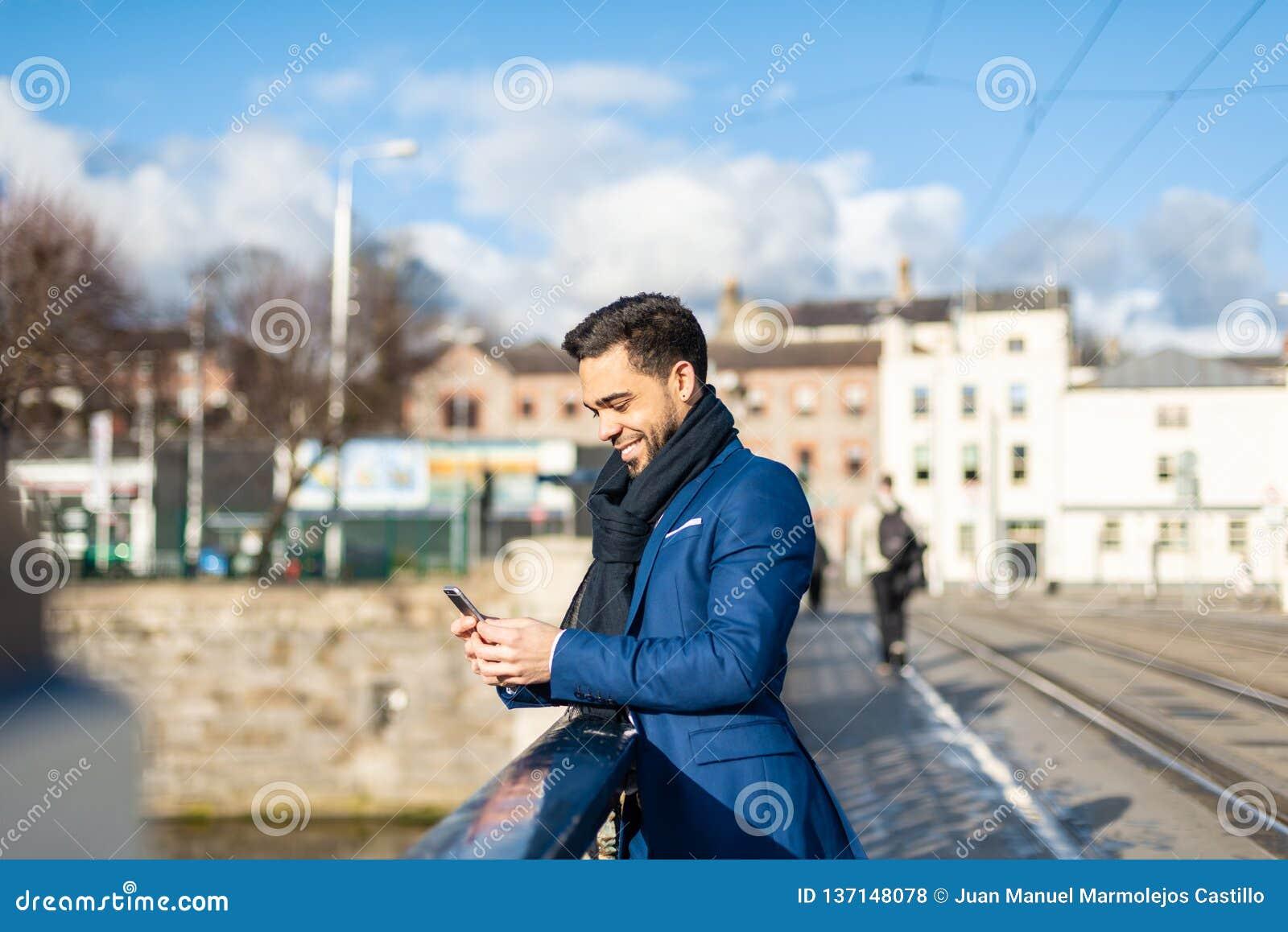 Homem de negócio que usa o telefone celular fora