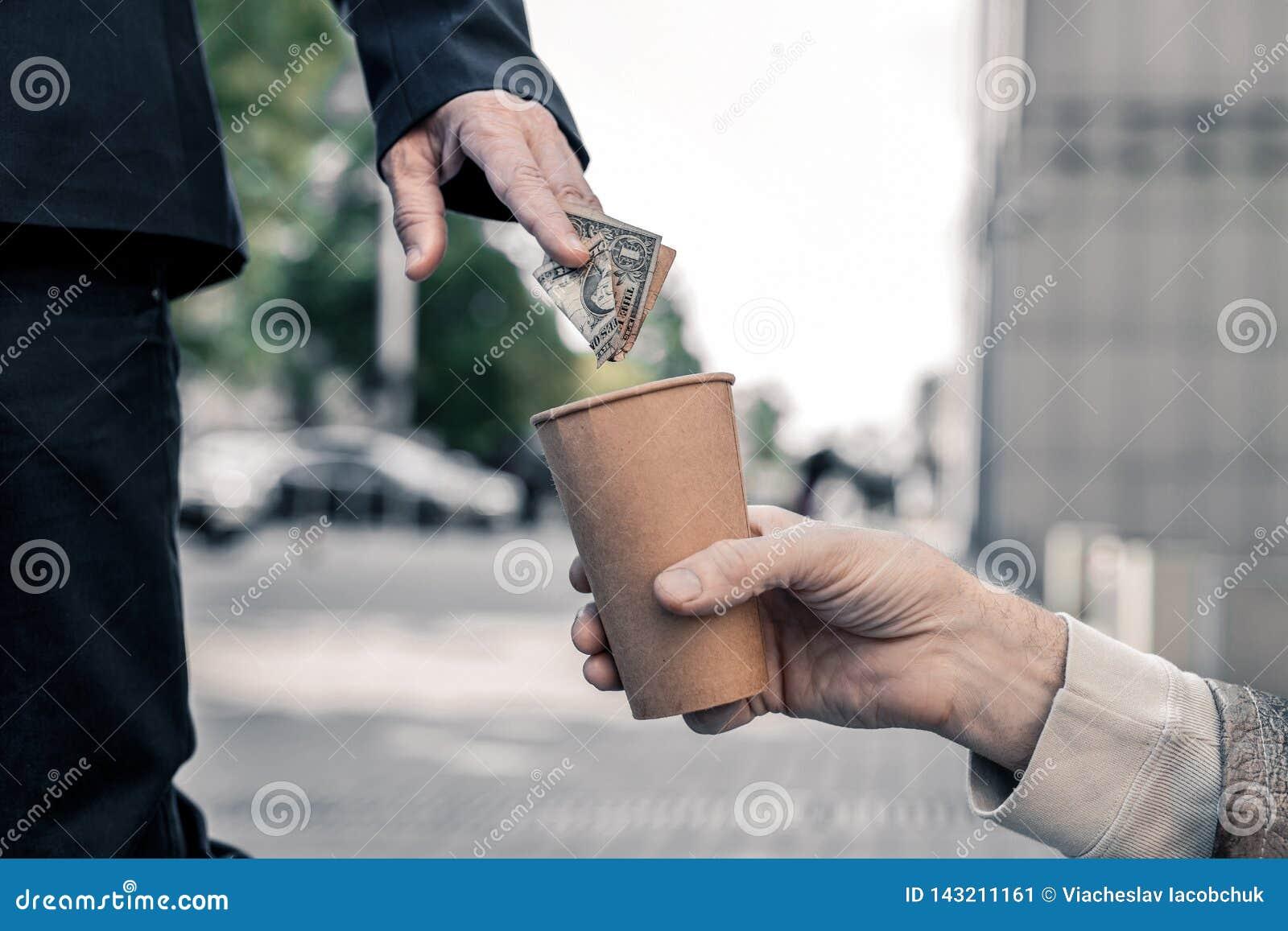 Homem de negócio rico que para na rua e que compartilha compassivomente do dinheiro