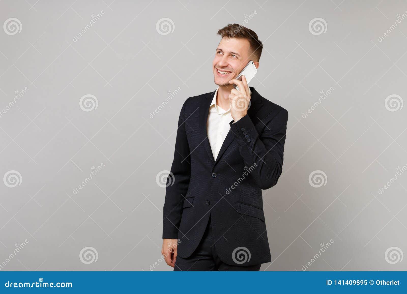 Homem de negócio de sorriso no terno clássico que olha de lado a fala no telefone celular que conduz a conversação agradável isol