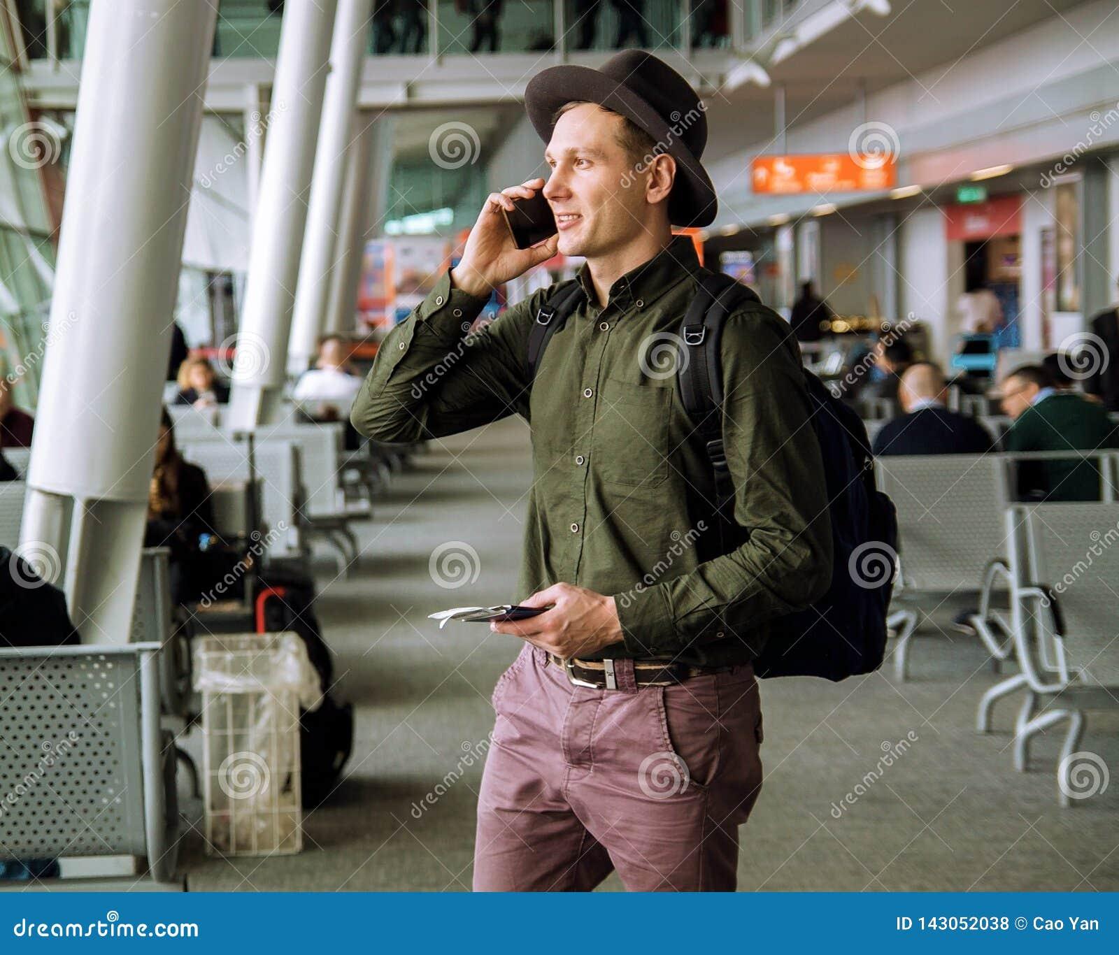 Homem de negócio urbano que fala no telefone esperto para dentro no aeroporto