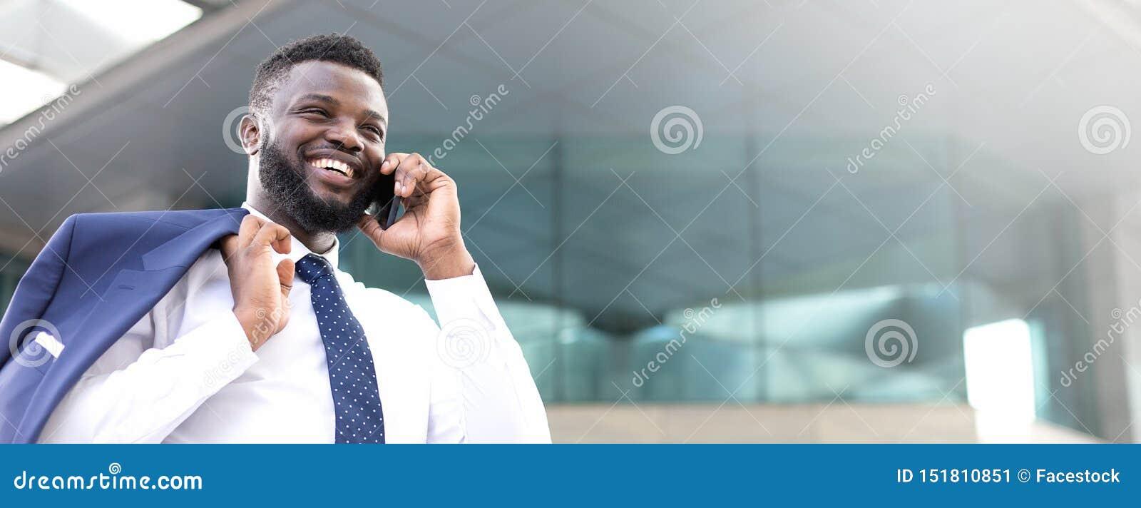 Homem de negócios africano feliz que guarda seu telefone ao estar perto da construção e ao olhar a direito