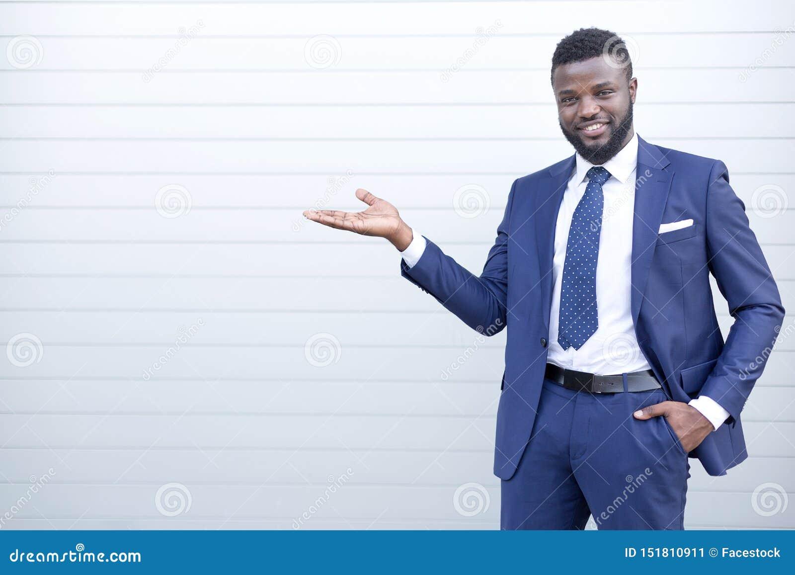 Homem de negócios africano feliz de sorriso no terno que está contra a parede que aponta a algo