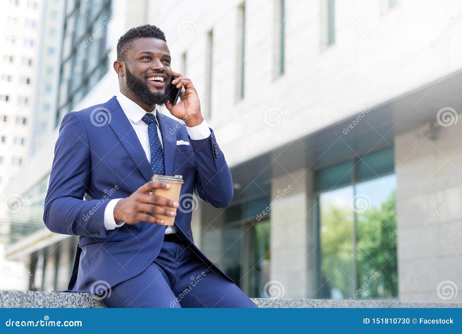 Homem de negócios africano novo que fala no telefone com uma xícara de café ao sentar a parte externa
