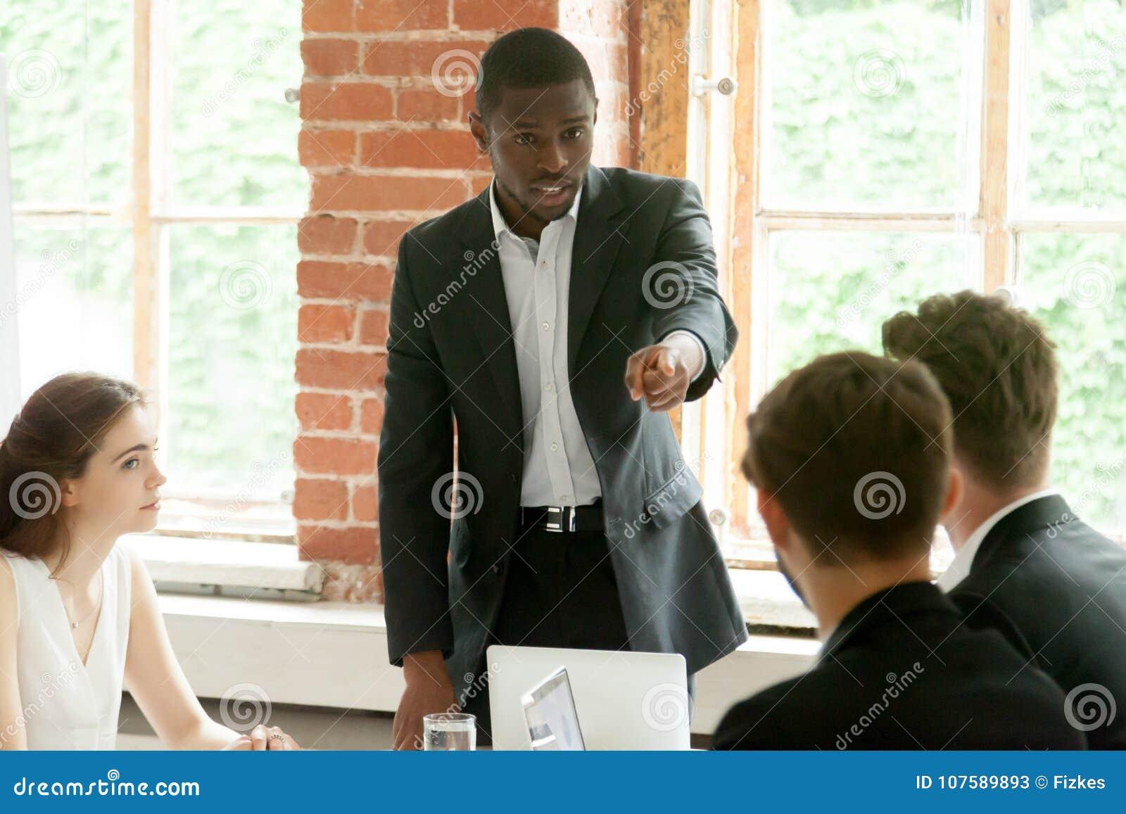 Homem de negócios africano rude que aponta o dedo no duri branco do colega