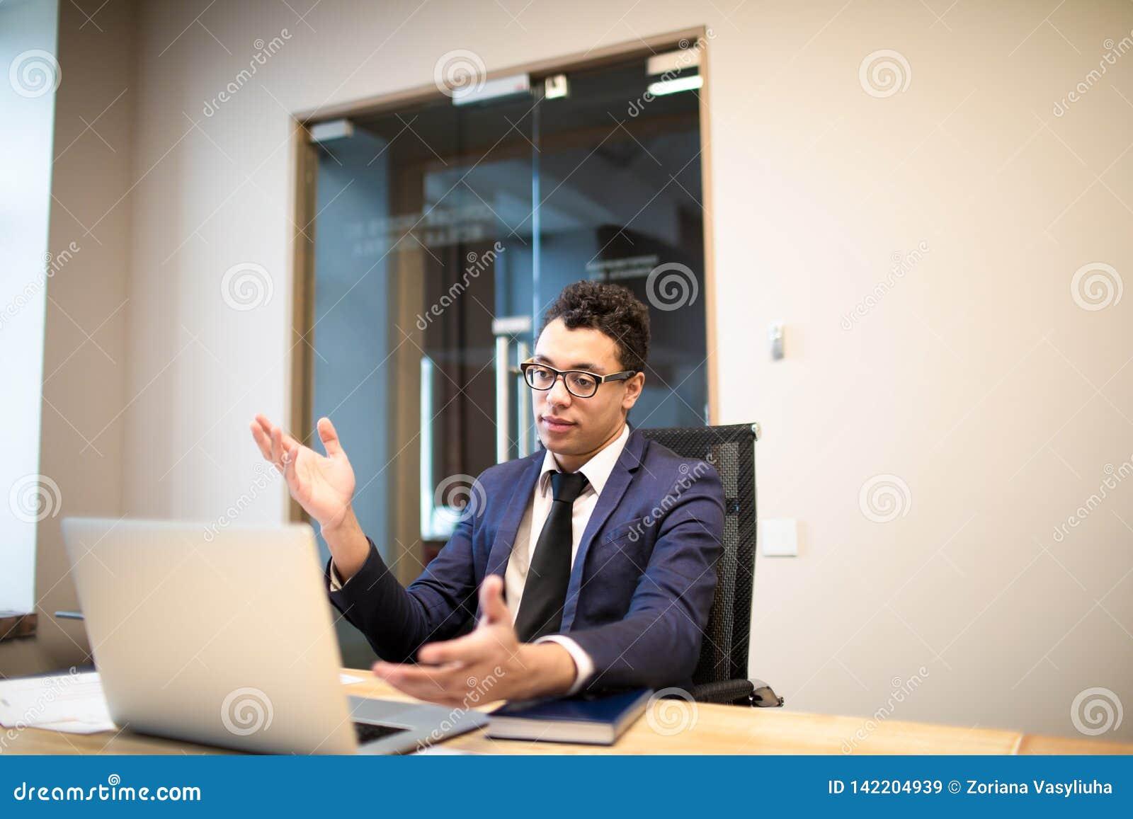 Homem de negócios afro-americano no terno oficial luxuoso que acumula a conversação video em linha no laptop com sócio internacio