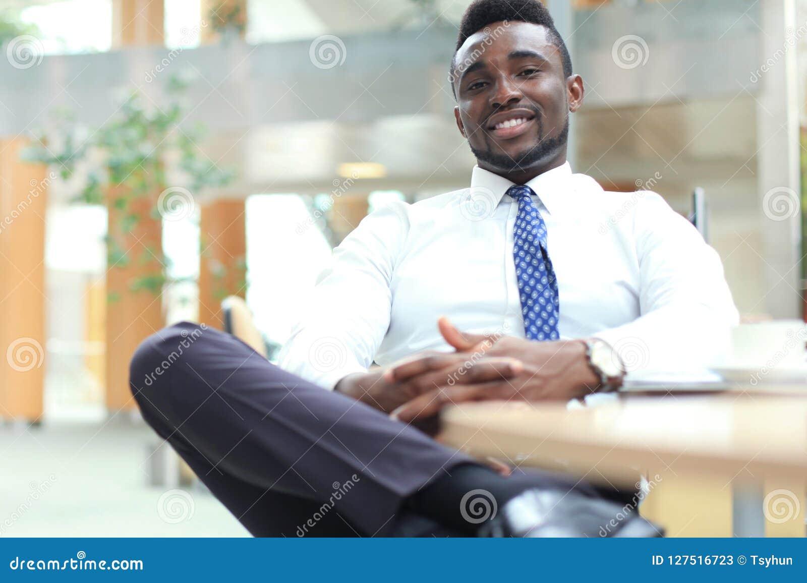 Homem de negócios afro-americano novo feliz que olha a câmera no local de trabalho no escritório