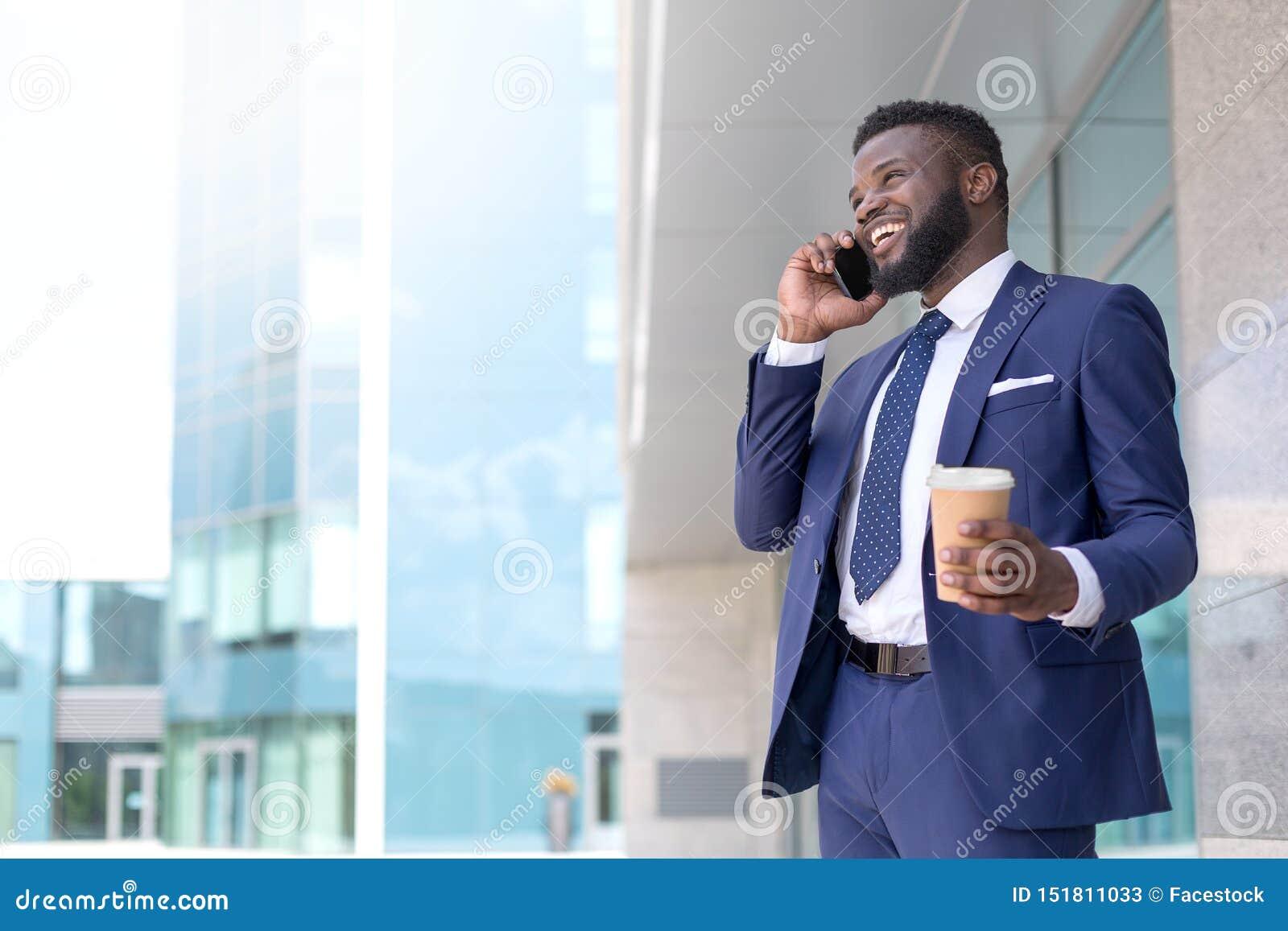 Homem de negócios afro-americano novo que fala a um cliente no telefone com um copo do coffe durante o tempo da ruptura Copie o e