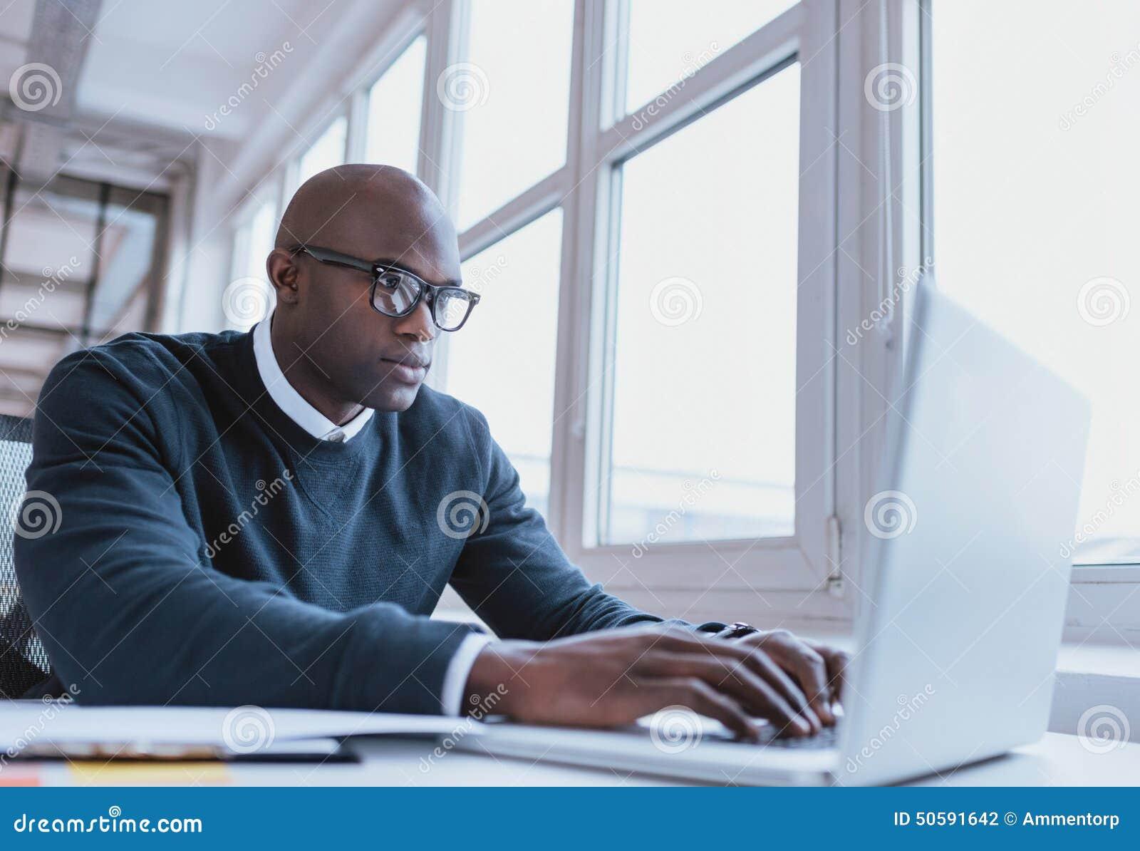 Homem de negócios afro-americano que trabalha em seu portátil