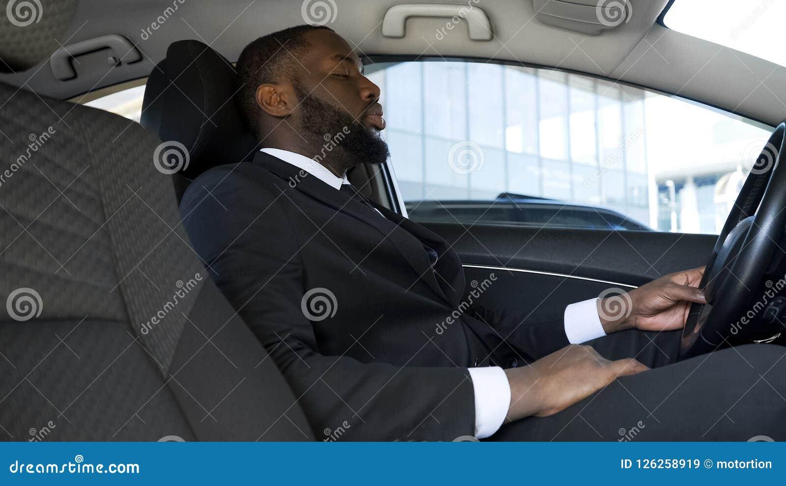 Homem de negócios afro-americano sobrecarregado que senta-se no carro, cansado após o dia fatigante