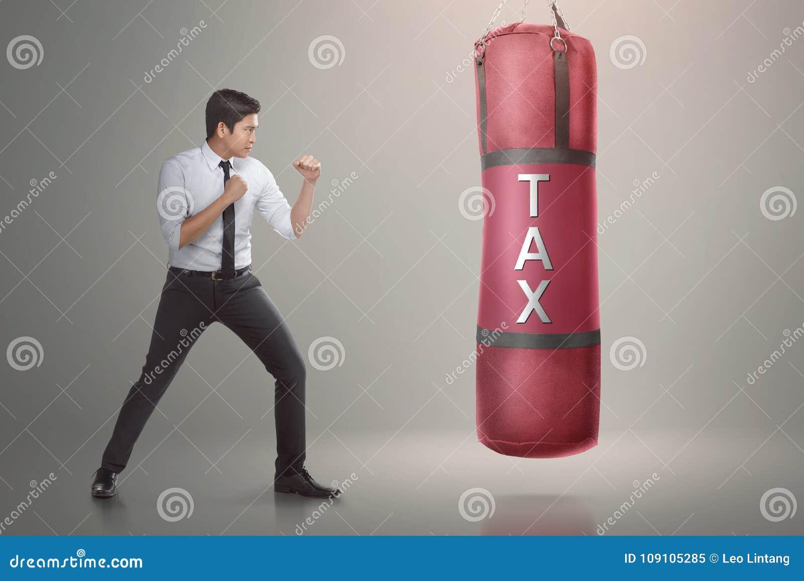 Homem de negócios asiático considerável pronto para perfurar o saco do encaixotamento com te do imposto