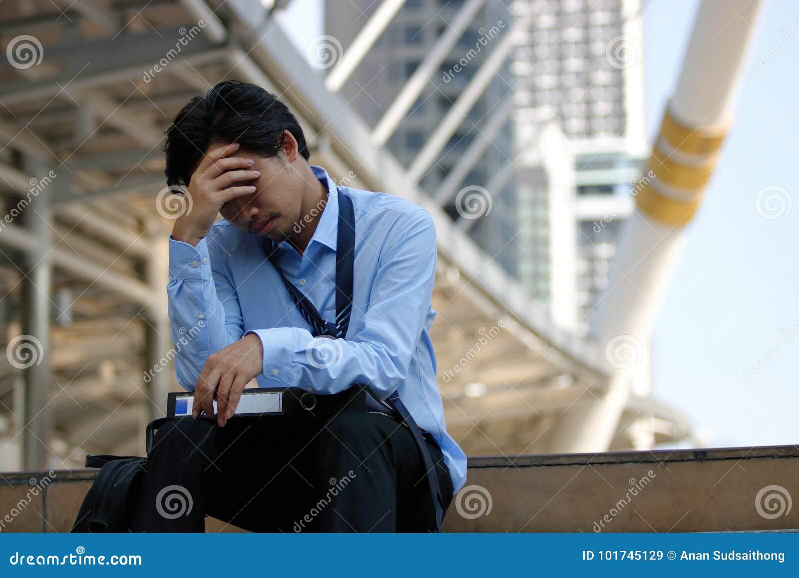 Homem de negócios asiático forçado frustrante com mão na testa que senta-se na escadaria na cidade Negócio deprimido do desempreg