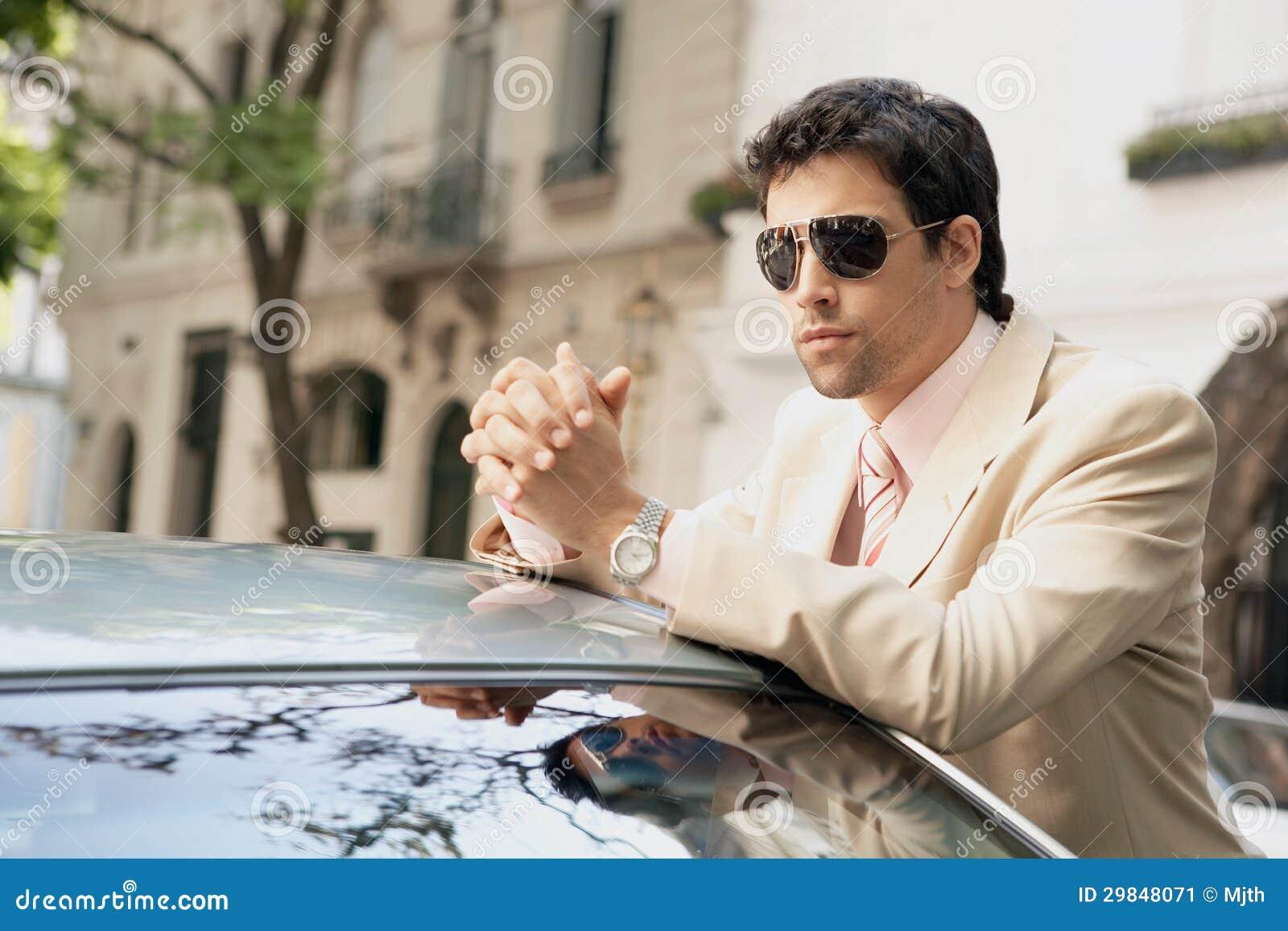 Homem de negócios que inclina-se no carro.