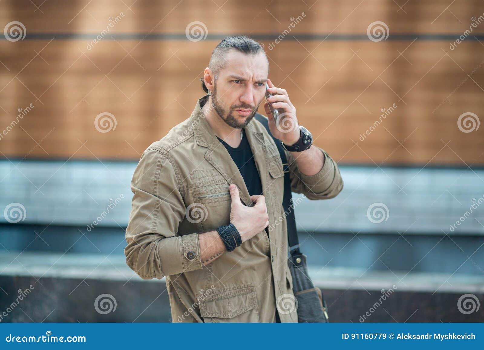 Homem de negócios atrativo que fala no smartphone